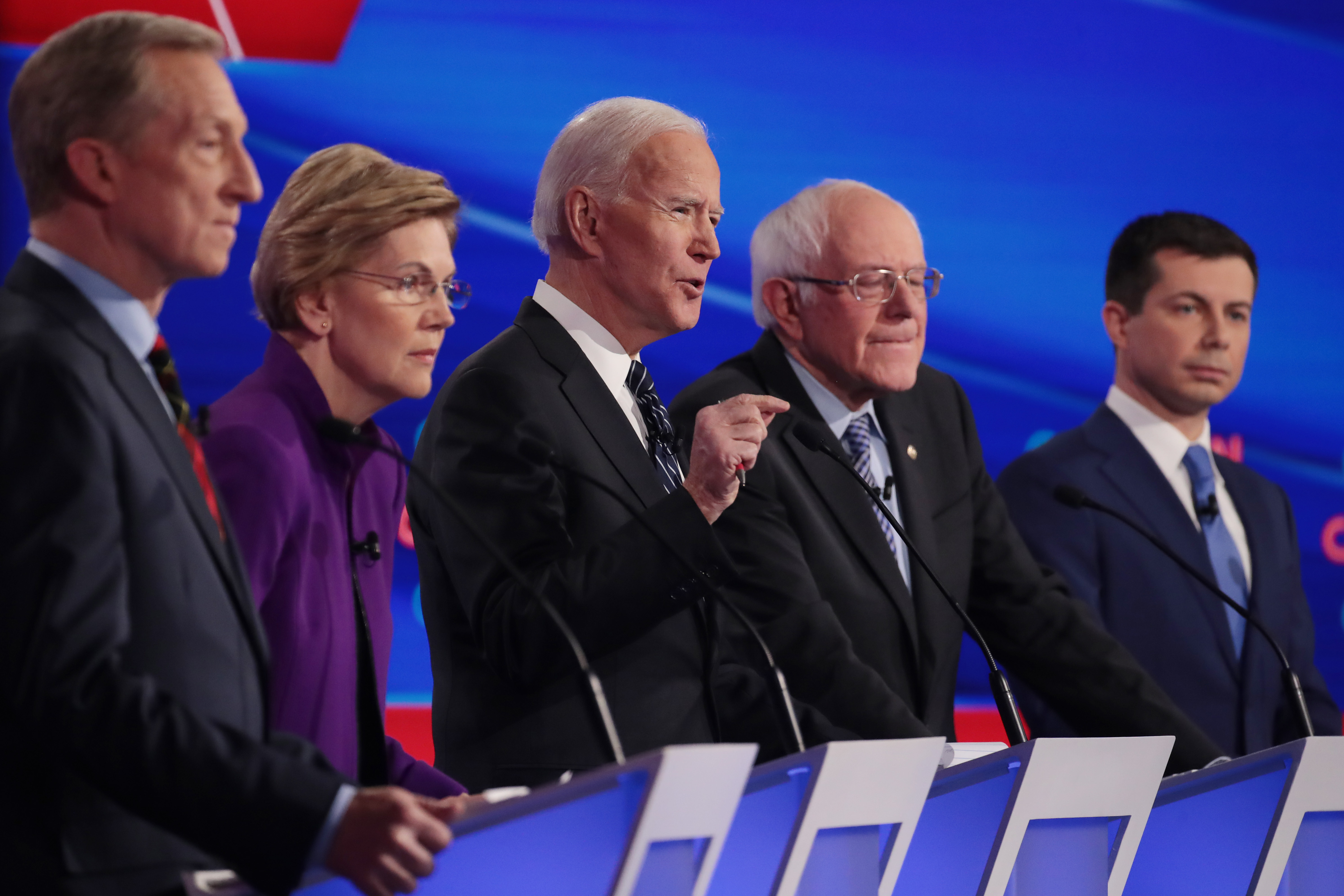 DES MOINES, IOWA - JANUARY 14: Tom Steyer (L), Sen. Elizabeth Warren (D-MA), Sen. Bernie Sanders (I-VT) and former South Bend, Indiana Mayor Pete Buttigieg (R) listen as former Vice President Joe Biden (C) speaks during the Democratic presidential primary debate at Drake University on January 14, 2020 in Des Moines, Iowa. Six candidates out of the field qualified for the first Democratic presidential primary debate of 2020, hosted by CNN and the Des Moines Register. (Photo by Scott Olson/Getty Images)