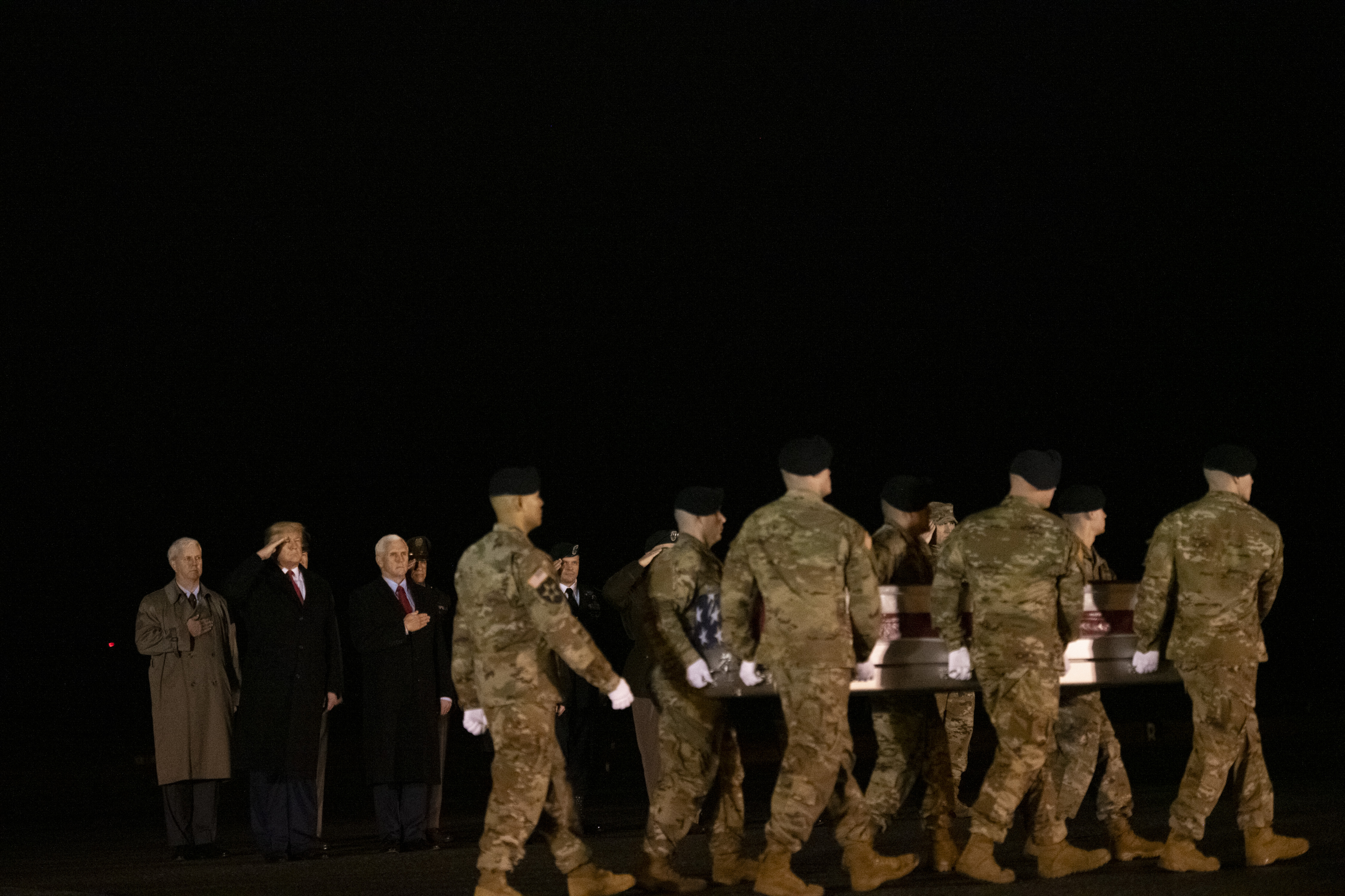 DOVER, DE - FEBRUARY 10: (L-R) U.S. President Donald J. Trump and Vice President Mike Pence watch as military personnel carry a transfer case for fallen service member, U.S. Army Sgt. 1st Class Javier J. Gutierrez, 28, during a dignified transfer at Dover Air Force Base on February 10, 2020 in Dover, Delaware. Gutierrez and U.S. Army Sgt. 1st Class Antonio R. Rodriguez were both killed in an attack in the Nangarhar province of Afghanistan on Saturday, according to a Department of Defense release. (Photo by Mark Makela/Getty Images)