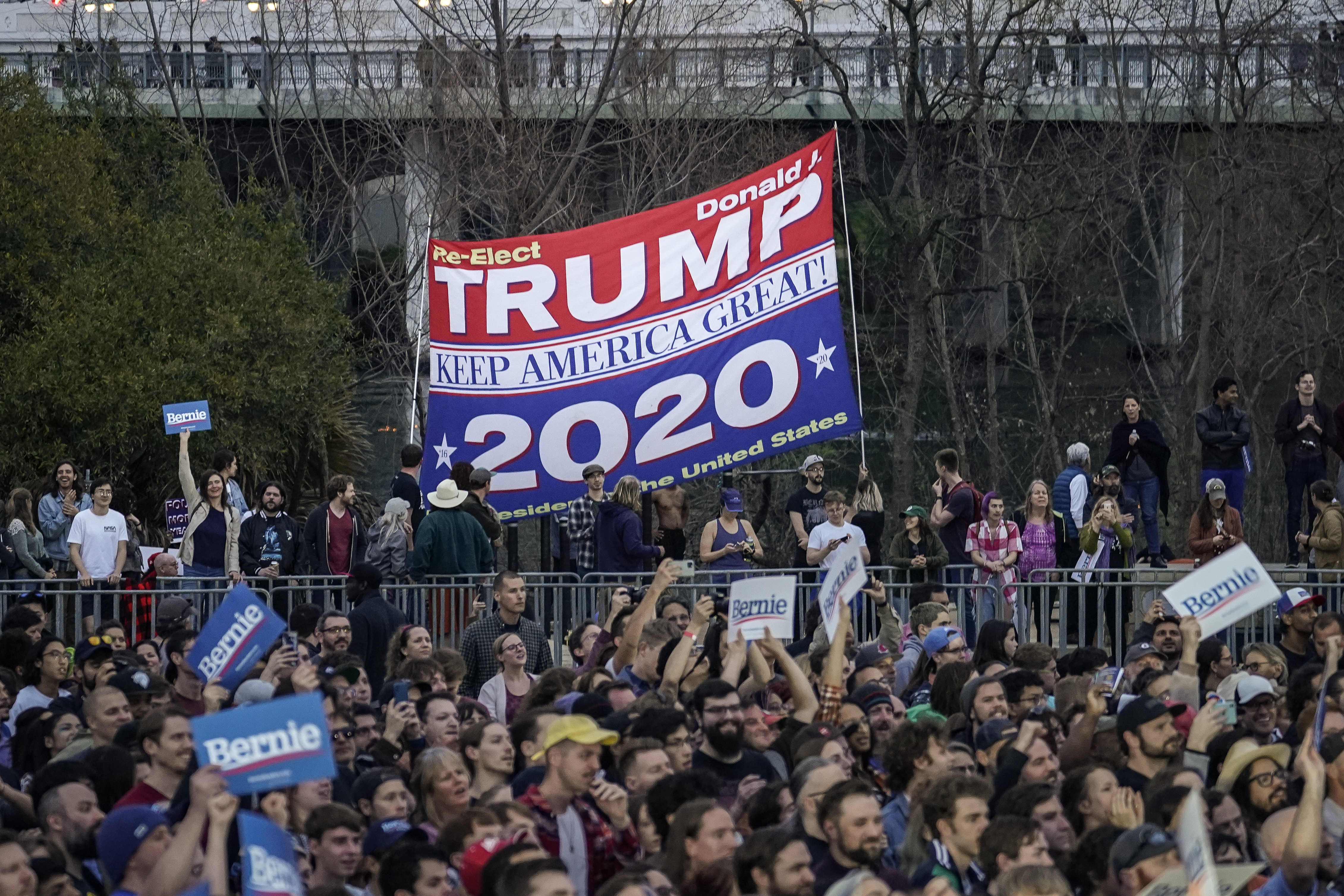 AUSTIN, TX - FEBRUARY 23: Supporters of President Donald Trump hold up a banner just outside the venue while Democratic presidential candidate Sen. Bernie Sanders (I-VT) speaks during a campaign rally at Vic Mathias Shores Park on February 23, 2020 in Austin, Texas. With early voting underway in Texas, Sanders is holding four rallies in the delegate-rich state this weekend before traveling on to South Carolina. Texas holds their primary on Super Tuesday March 3rd, along with over a dozen other states. (Photo by Drew Angerer/Getty Images)