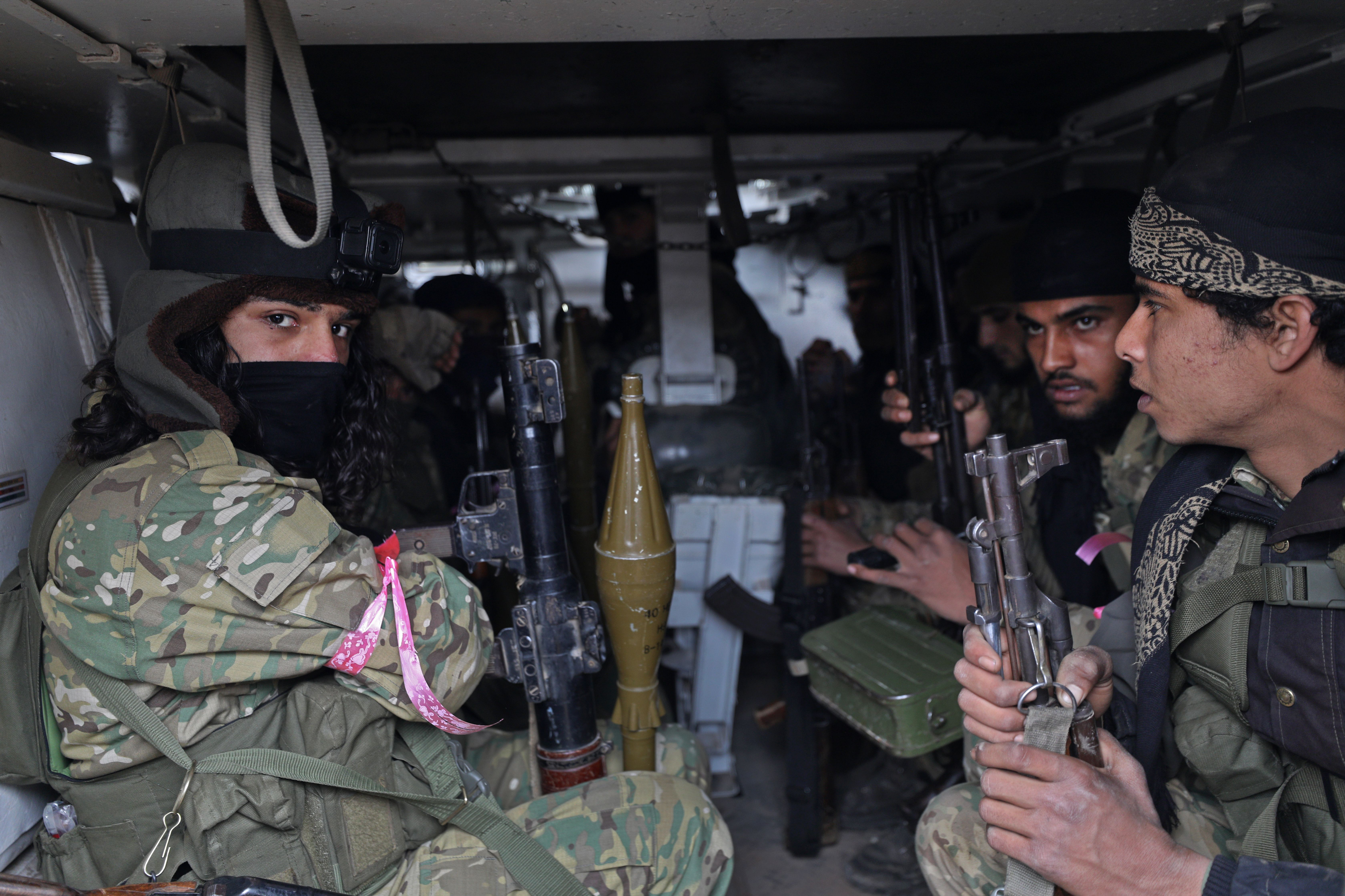 "Members of the ""Syrian National Army"", an alliance of Turkey-backed rebel groups, ride in an armoured personnel carrier (APC) in the town of Sarmin, about 8 kilometres southeast of the city of Idlib in northwestern Syria, on February 24, 2020, as they take part in a military offensive on the village of Nayrab following an artillery barrage fired by Turkish forces. (Photo by OMAR HAJ KADOUR/AFP via Getty Images)"