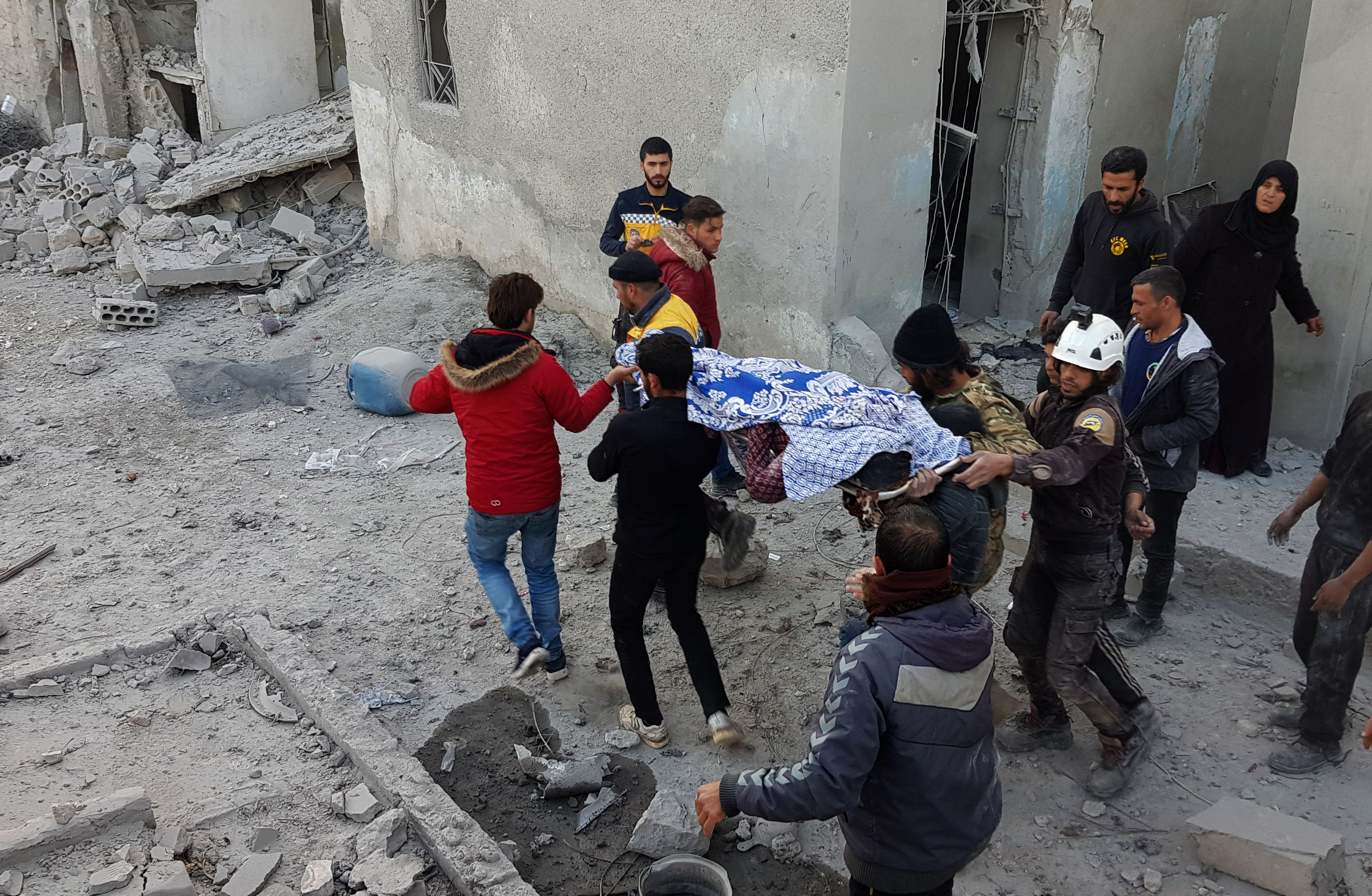 Civilians and rescuers carry the body of a victim following pro-regime forces air strikes in the town of Binnish in Syrias northwestern Idlib province, near the border with Turkey on February 25, 2020. (Photo by MUHAMMAD HAJ KADOUR/AFP via Getty Images)
