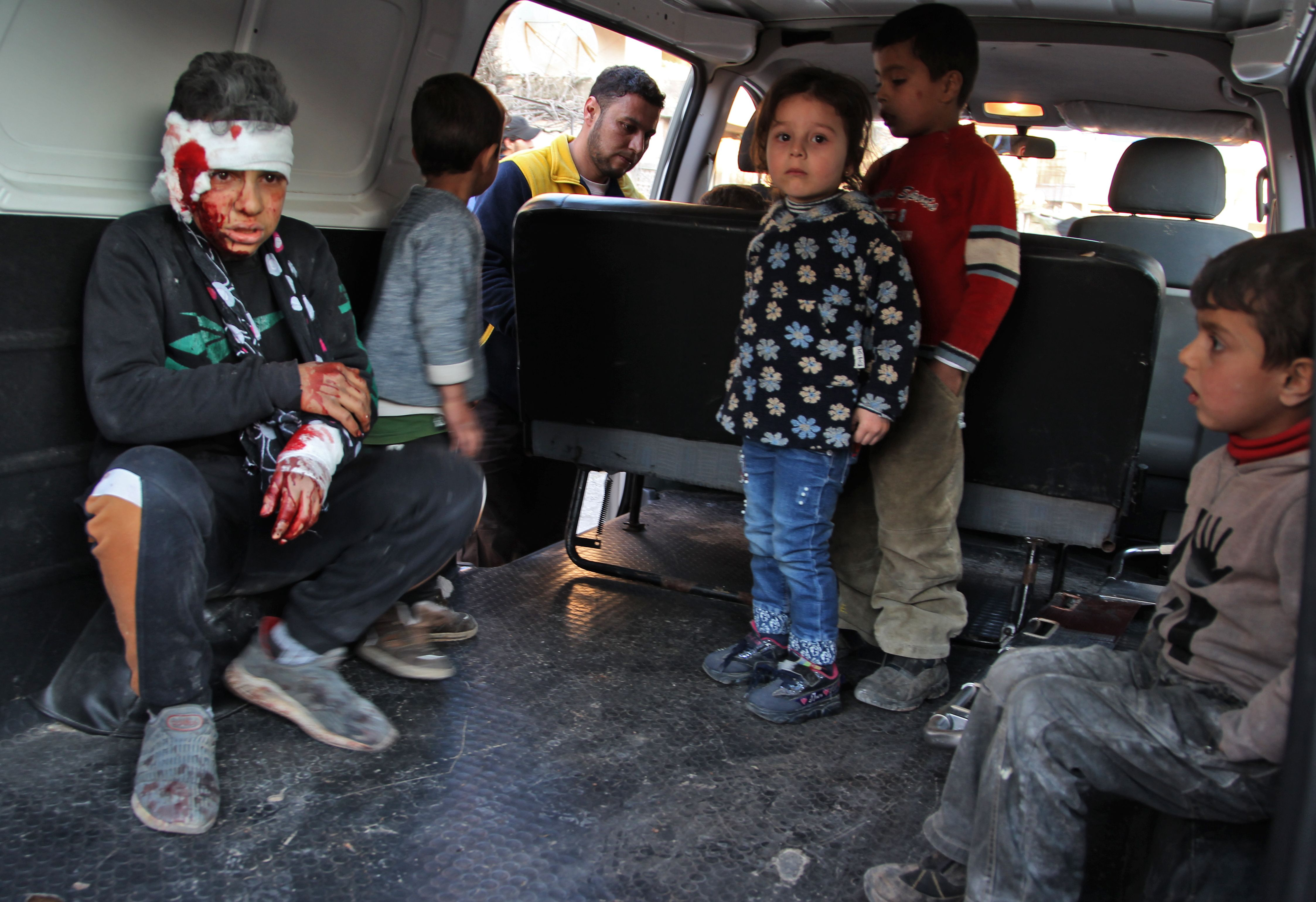 TOPSHOT - Graphic content / Syrian children sit inside a vehicle as they are evacuated from the scene of a pro-regime forces air strike in the town Maarrat Misrin in Syrias northwestern Idlib province, on February 25, 2020. (Photo by ABDULAZIZ KETAZ/AFP via Getty Images)