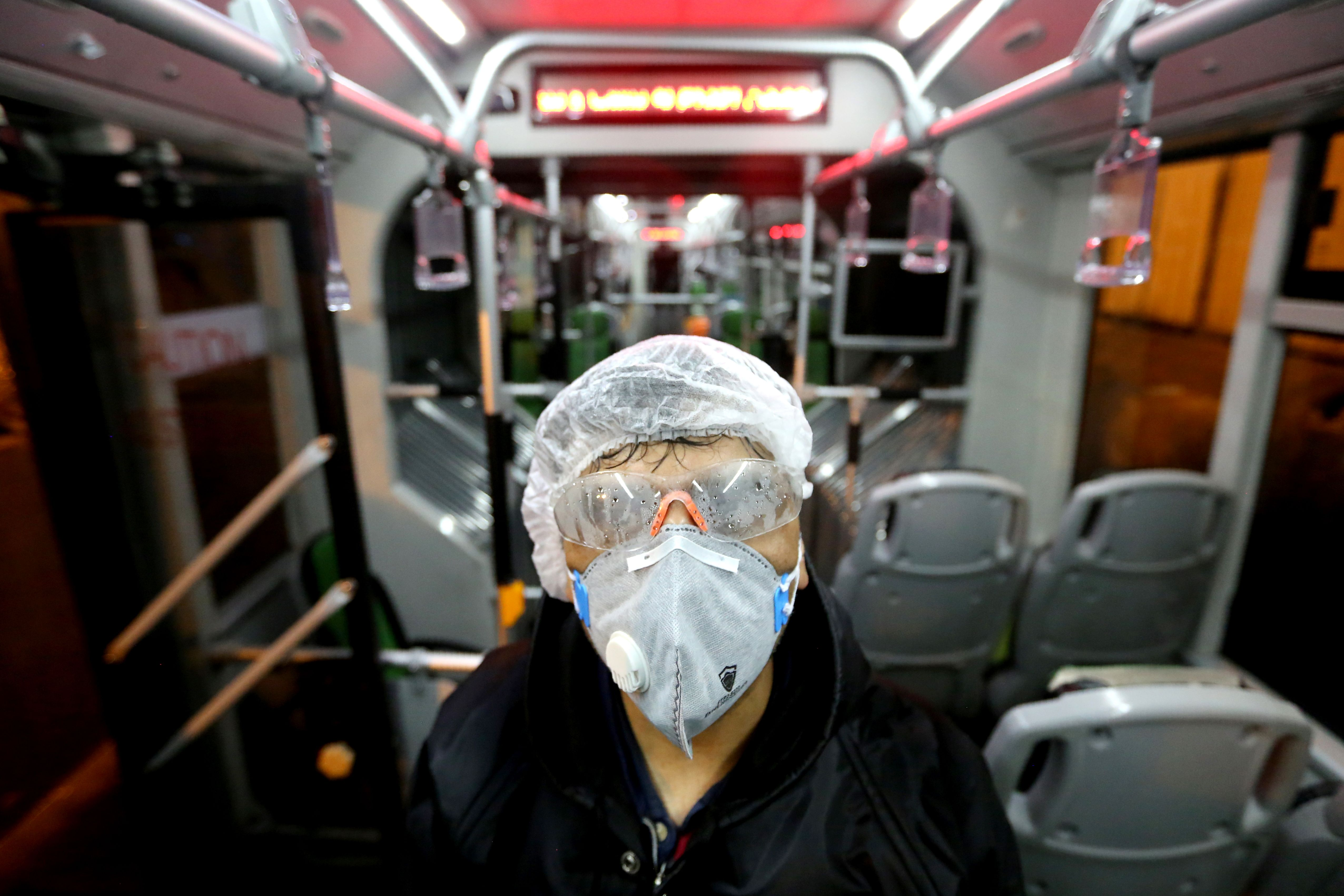 A Tehran Municipality worker cleans a bus to avoid the spread of the COVID-19 illness on (Photo by ATTA KENARE/AFP via Getty Images)