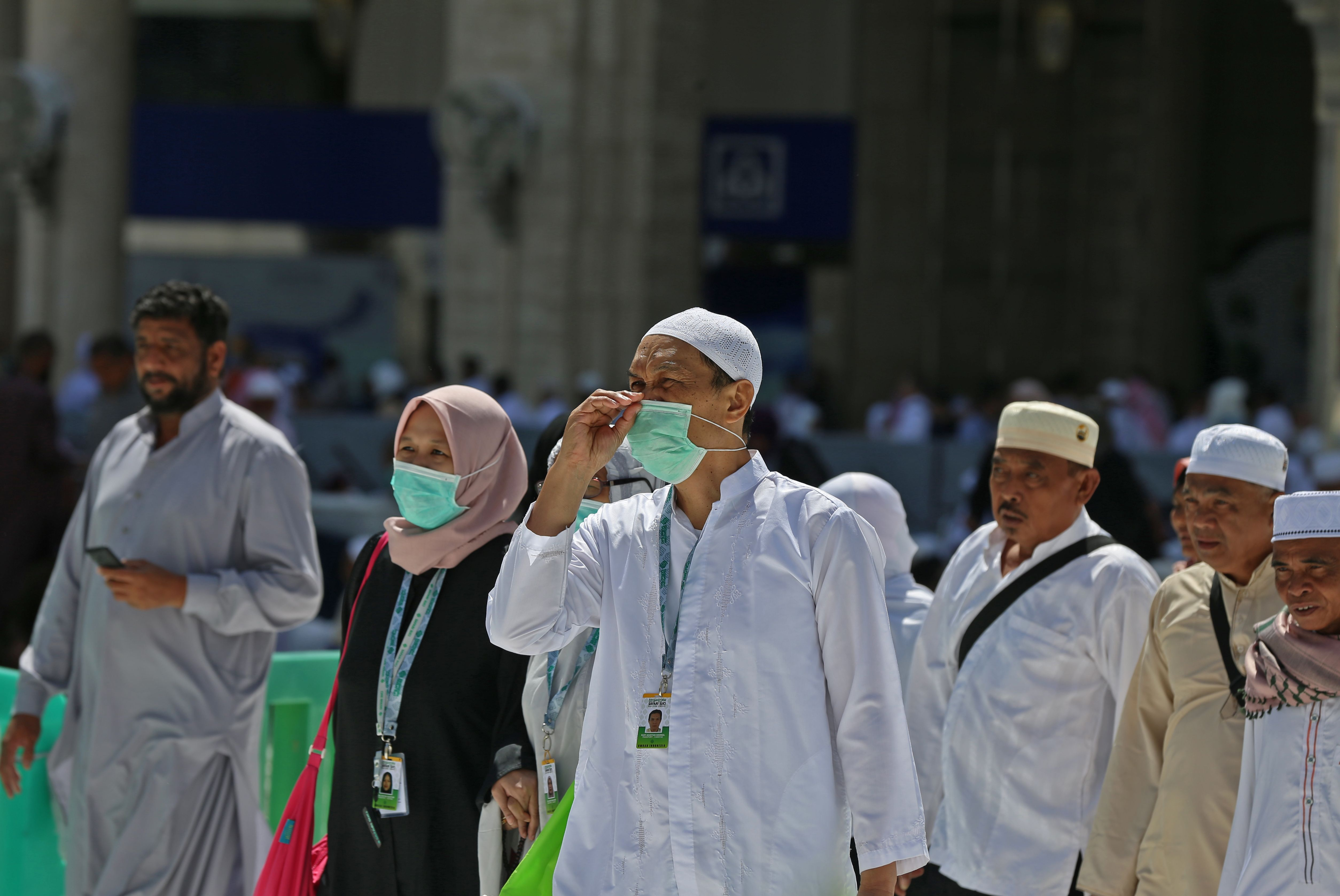 Muslim pilgrims wear masks at the Grand Mosque in Saudi Arabia's holy city of Mecca (Photo by ABDULGANI BASHEER/AFP via Getty Images)
