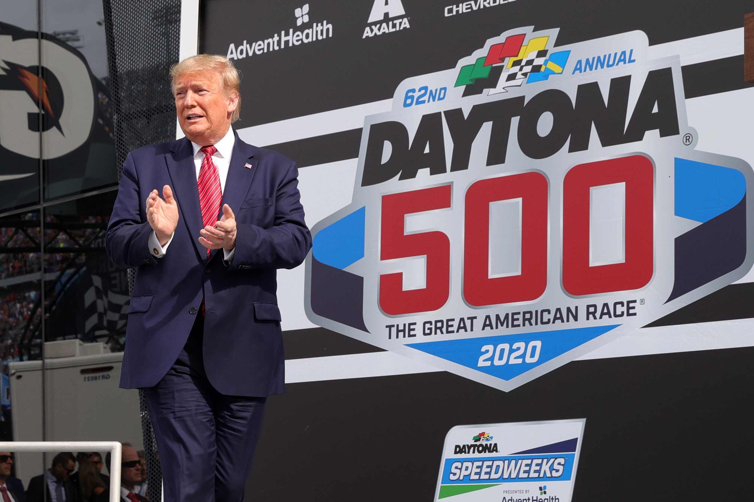 DAYTONA BEACH, FLORIDA - FEBRUARY 16: U.S. President Donald Trump speaks as First Lady Melania Trump looks on from Victory Lane prior to the NASCAR Cup Series 62nd Annual Daytona 500 at Daytona International Speedway on February 16, 2020 in Daytona Beach, Florida. (Photo by Chris Graythen/Getty Images)