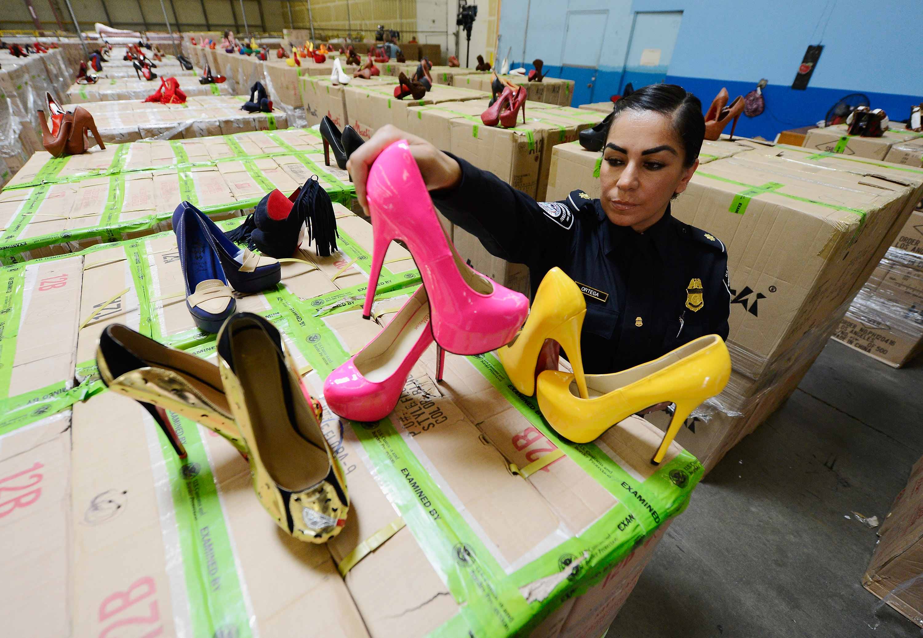 LONG BEACH, CA - AUGUST 16: U.S. Customs and Border Protection officer Elizabeth Ortega displays counterfeit Louboutin pumps and high heels featuring the distinctive red sole of French designer Christian Louboutin are displayed at Price Transfer Warehouse on August 16, 2012 in Long Beach, California. Between July 27 and Aug. 14, import specialists and officers assigned to the Los Angeles and Long Beach seaport have seized a total of five shipments from China containing more than 20,000 pairs in violation of the French designer's trademark with a potential retail value of $18 million. (Photo by Kevork Djansezian/Getty Images)