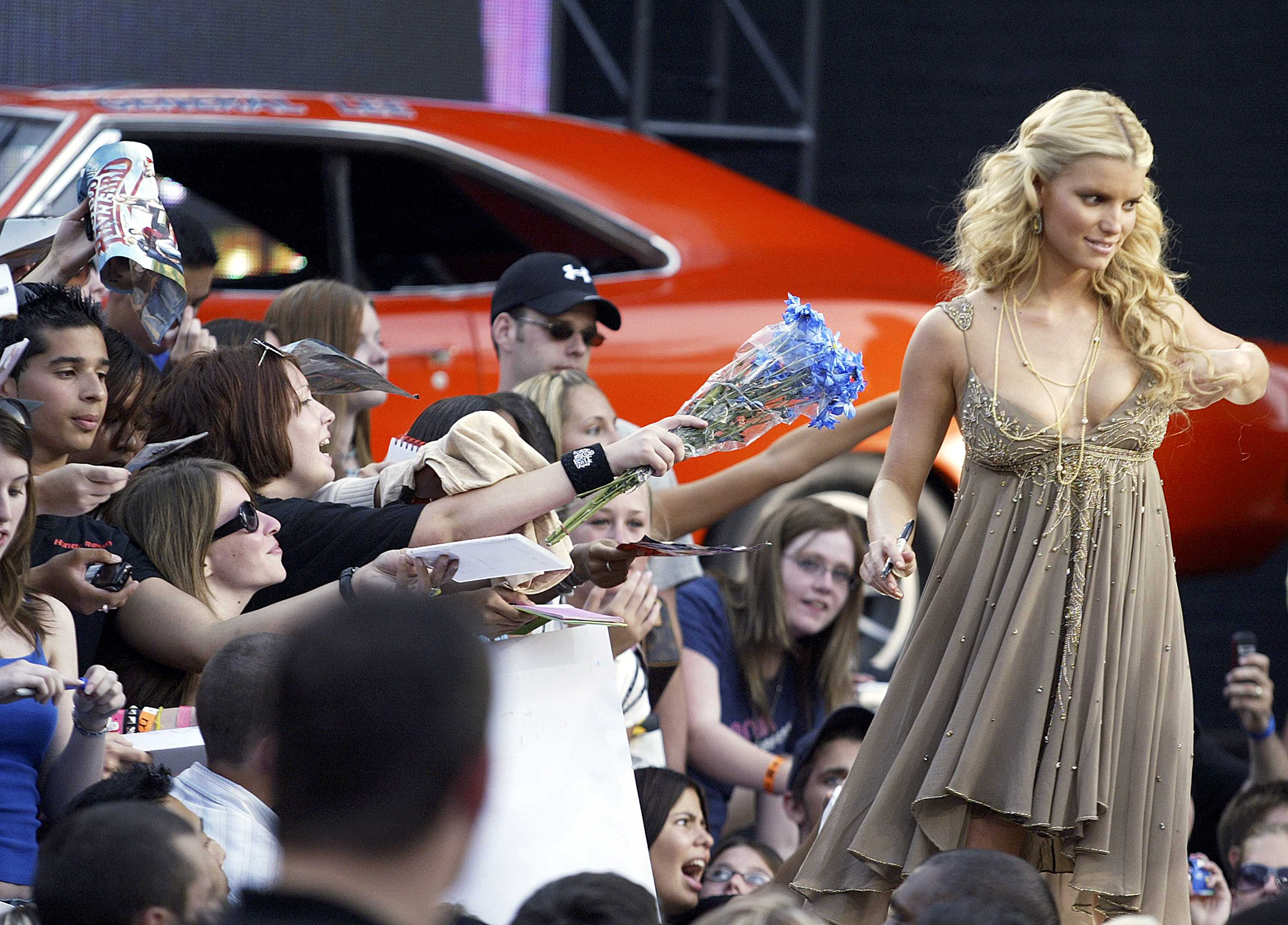 """TORONTO - JULY 31: Actress Jessica Simpson signs autographs for fans during an appearance on Canadian television to promote the new action comedy """"The Dukes of Hazzard"""", featuring Johnny Knoxville, Seann William Scott and Jessica Simpson on July 31, 2005 in Toronto, Canada. (Photo by Donald Weber/Getty Images)"""