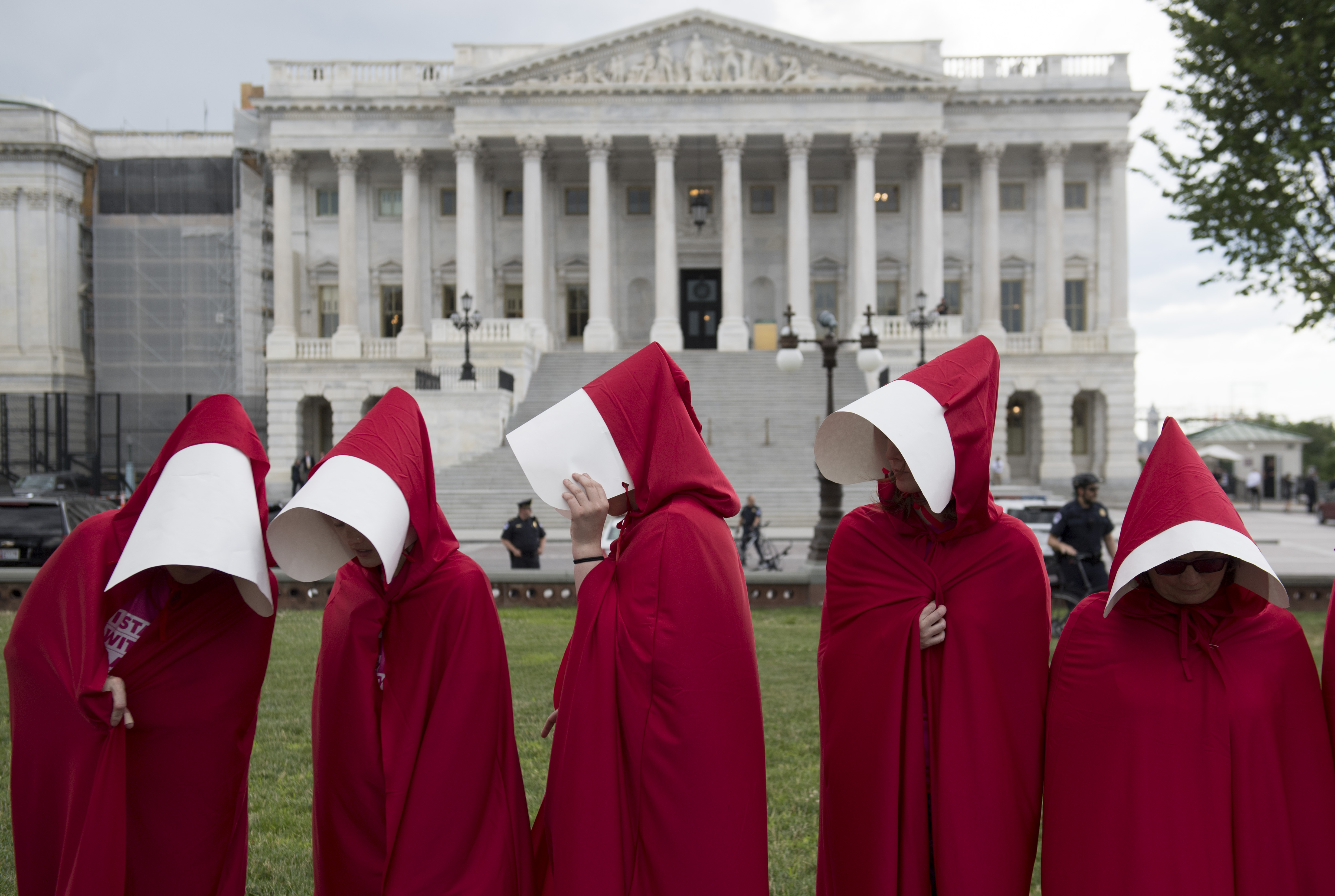 "Supporters of Planned Parenthood dressed as characters from ""The Handmaid's Tale,"" hold a rally as they protest the US Senate Republicans' healthcare bill outside the US Capitol in Washington, DC, June 27, 2017. / AFP PHOTO / SAUL LOEB (Photo credit should read SAUL LOEB/AFP via Getty Images)"