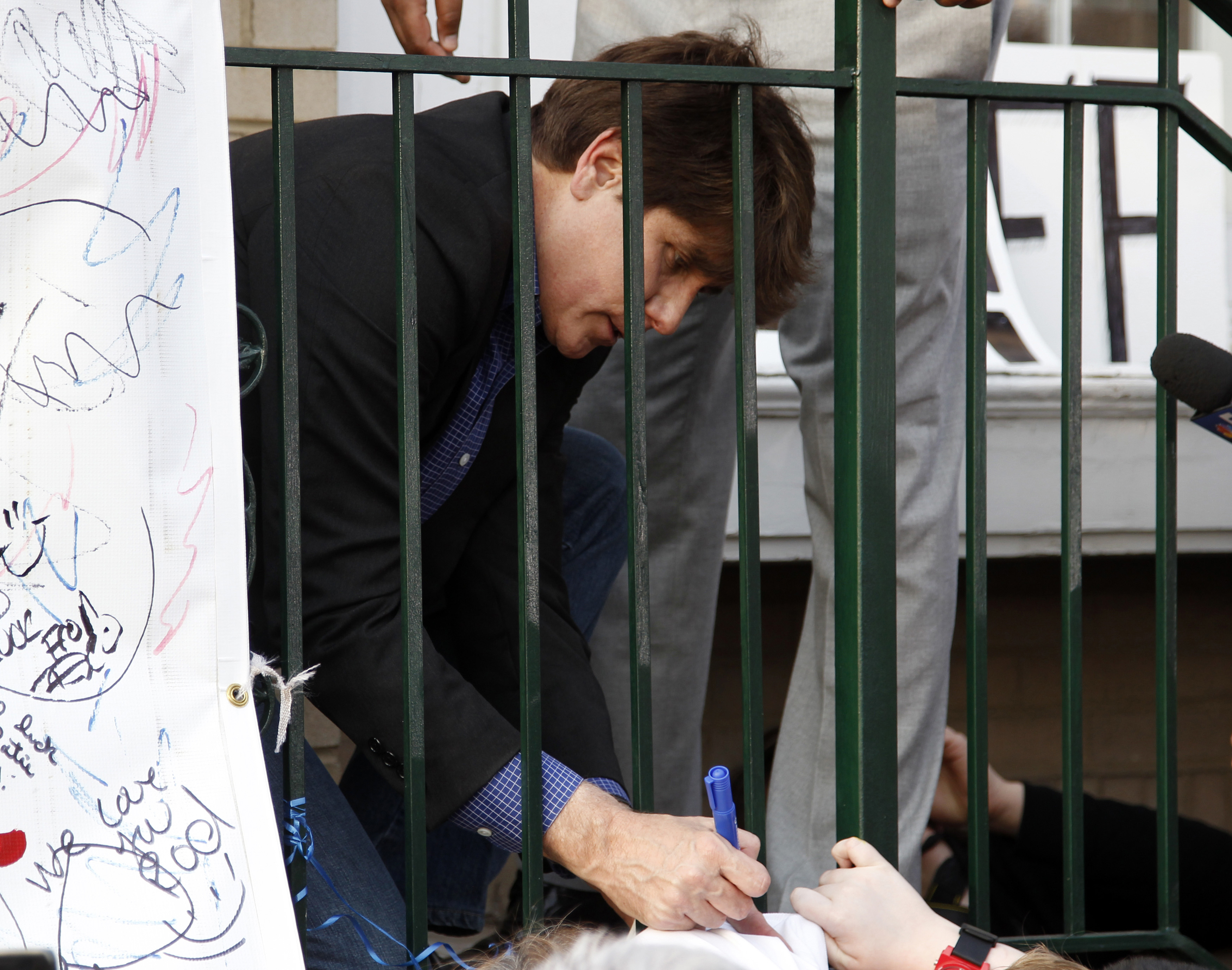 Former Illinois Governor Rod Blagojevich signs autographs on his front porch after making a statement to reporters outside his Chicago home one day before reporting to federal prison in Colorado to serve a 14-year sentence for corruption, March 14, 2012. REUTERS/Jeff Haynes