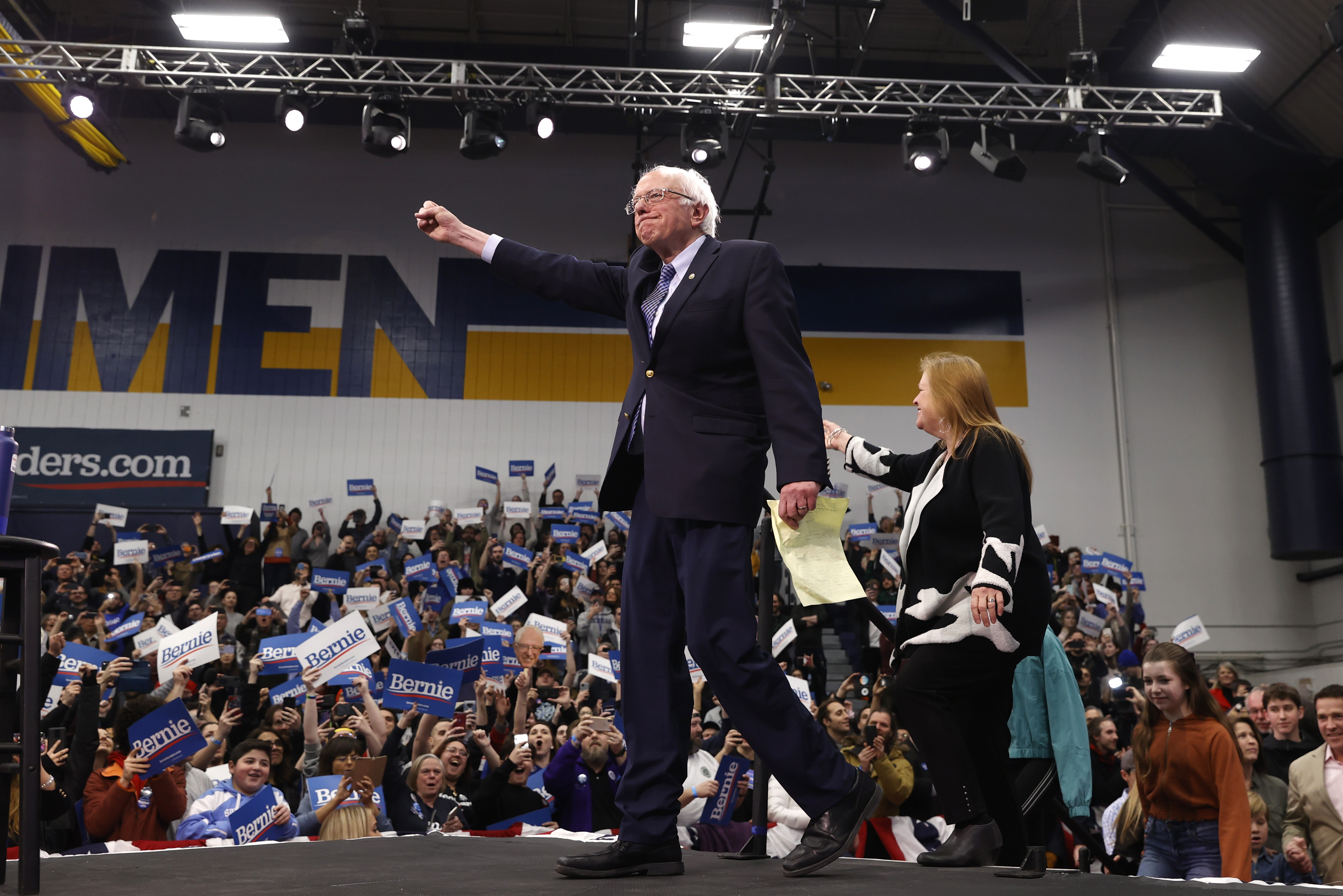 Democratic U.S. presidential candidate Senator Bernie Sanders pumps his fist and is accompanied by his wife Jane O'Meara Sanders as he arrives to speak at his New Hampshire primary night rally in Manchester, N.H., U.S., February 11, 2020. REUTERS/Mike Segar - HP1EG2C0E5I9E