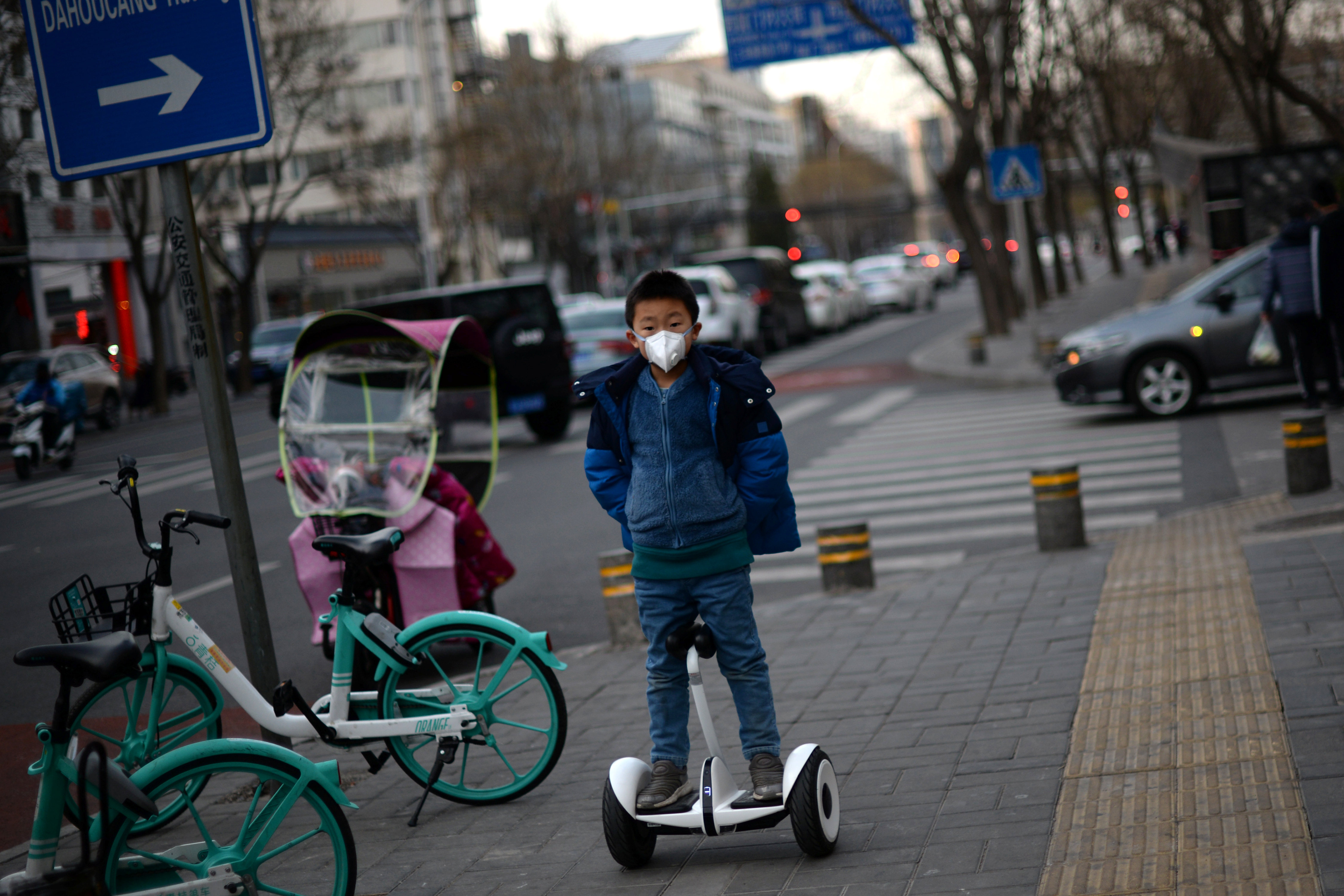 A child wearing a face mask rides a smart self-balancing scooter on a street, as the country is hit by an outbreak of the novel coronavirus, in Beijing, China February 18, 2020. REUTERS/Tingshu Wang - RC203F9P67JO