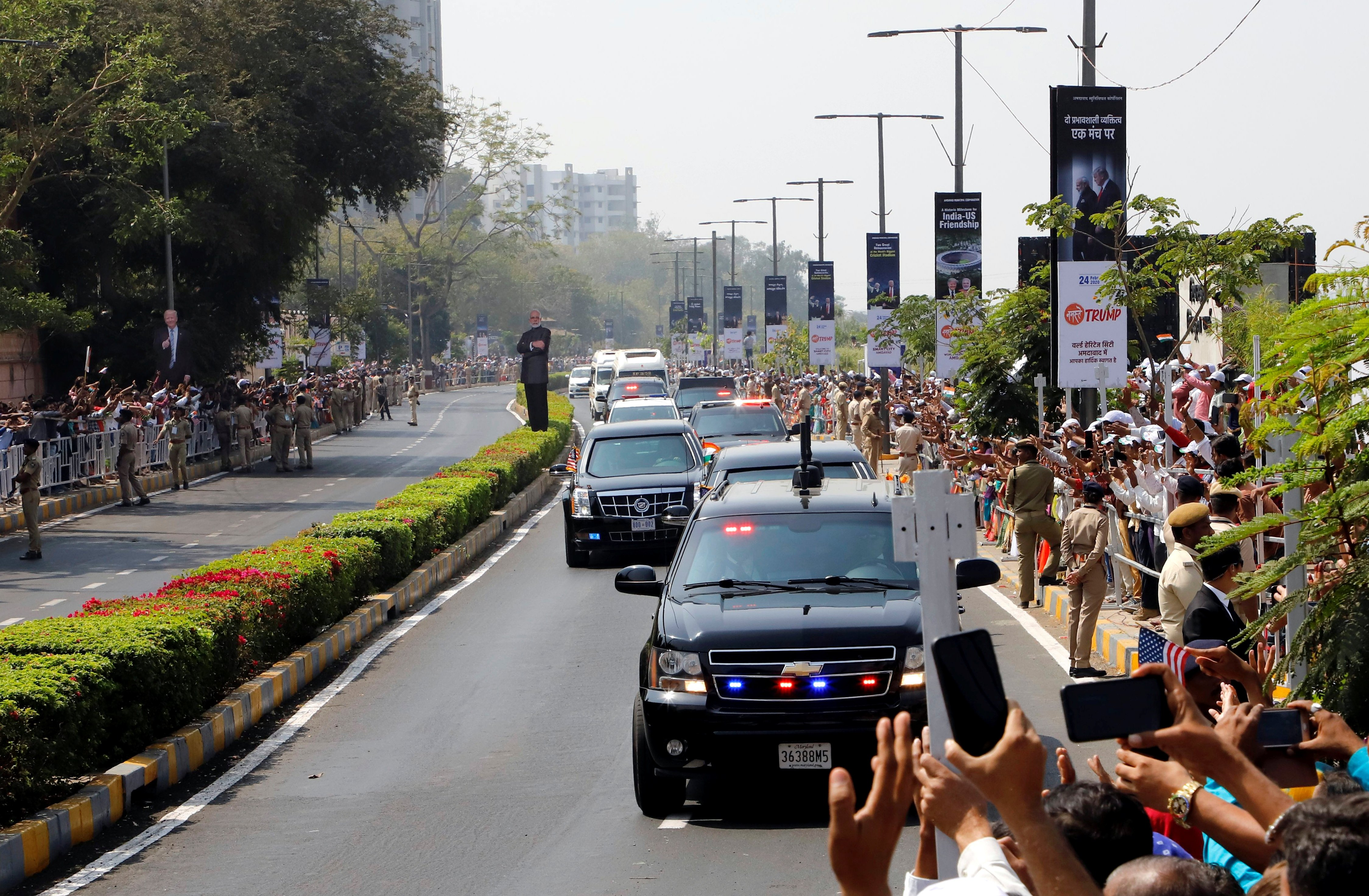 People wave as a motorcade transporting U.S. President Donald Trump and first lady Melania Trump passes enroute to Gandhi Ashram in Ahmedabad, India, February 24, 2020. (REUTERS/Stringer)