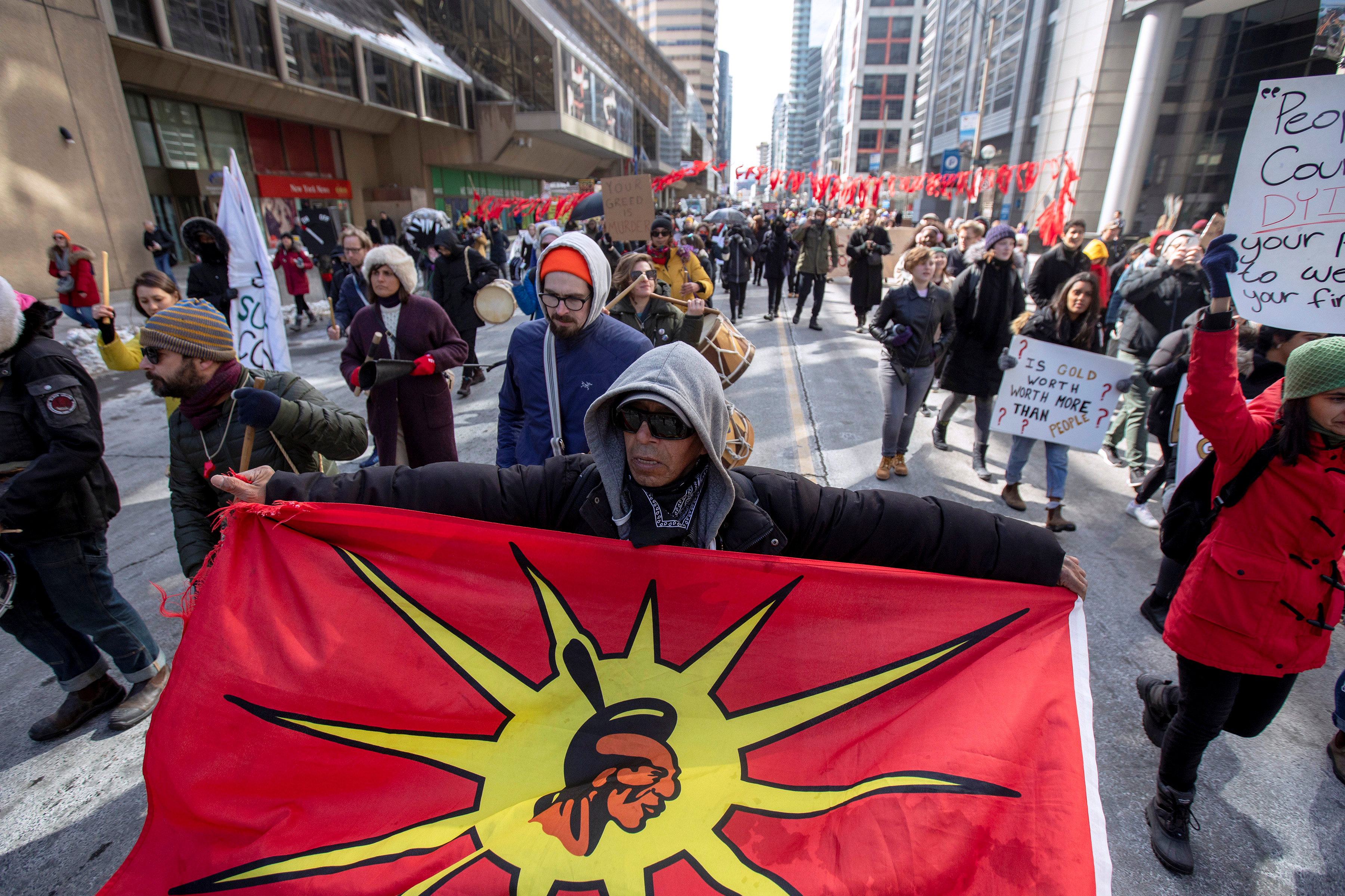 A protester holds a Mohawk Warrior Society flag as others march near the Prospectors & Developers Association of Canada (PDAC) convention to condemn mining practices in Toronto, Ontario, Canada March 1, 2020. REUTERS/Carlos Osorio