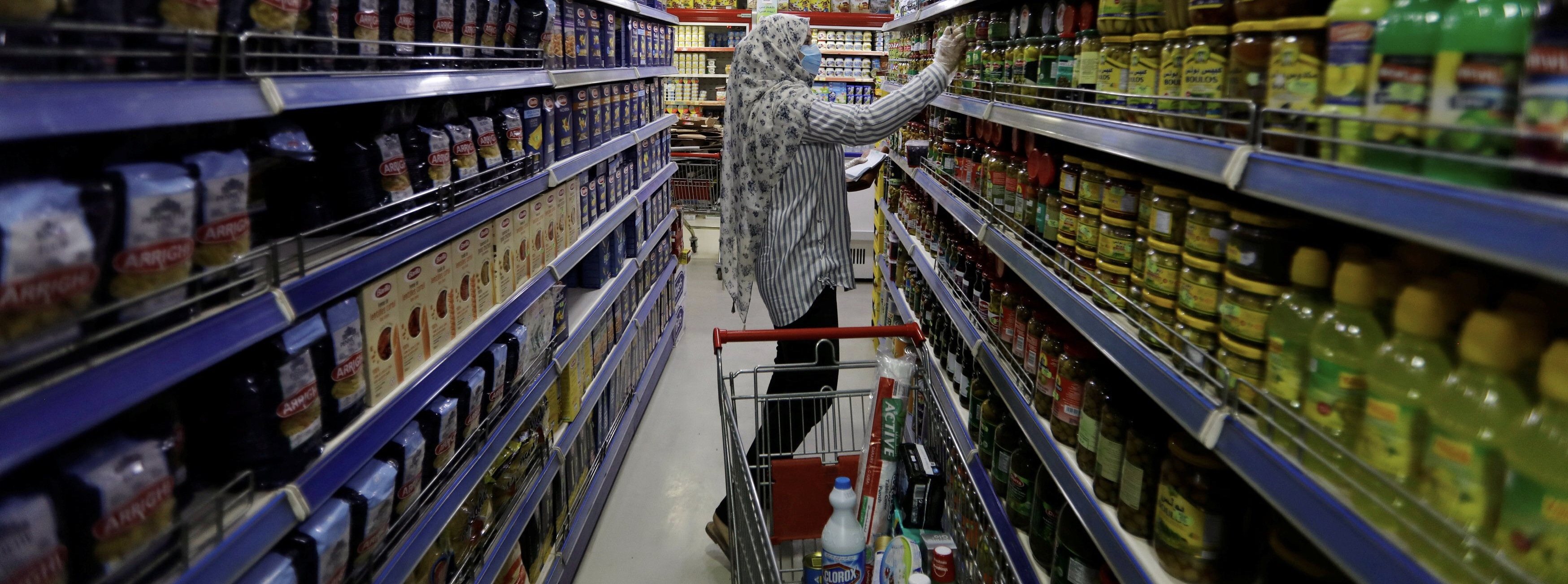 A woman wears a protective face mask and gloves, as she shops at a supermarket before curfew, following the outbreak of coronavirus, in Baghdad, Iraq March 17, 2020. REUTERS/Khalid al-Mousily
