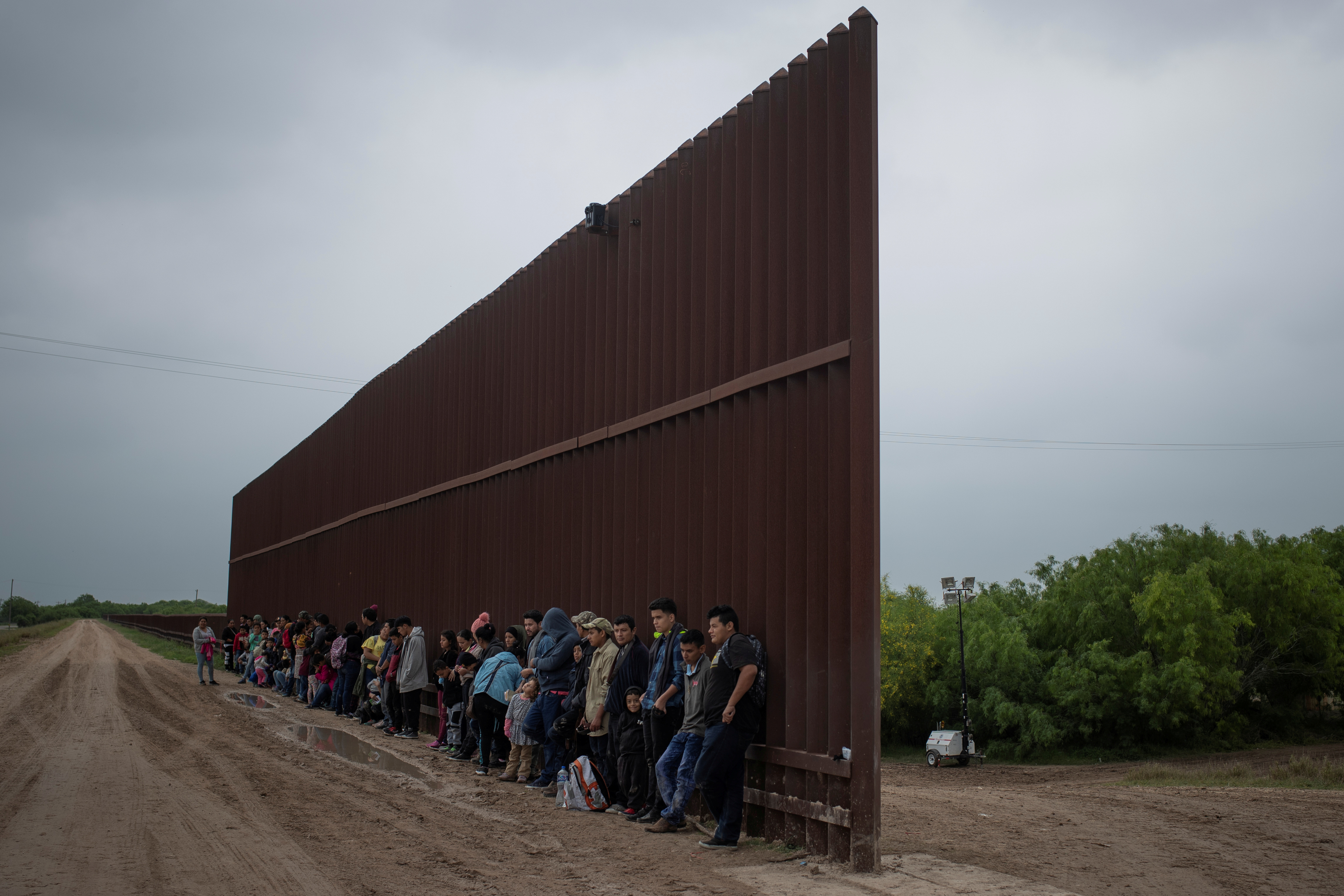 FILE PHOTO: Asylum-seeking migrants from Central America line-up along the border wall as they wait to surrender to the U.S. border patrol, after they crossed the Rio Grande river into the United States from Mexico, in Penitas, Texas,