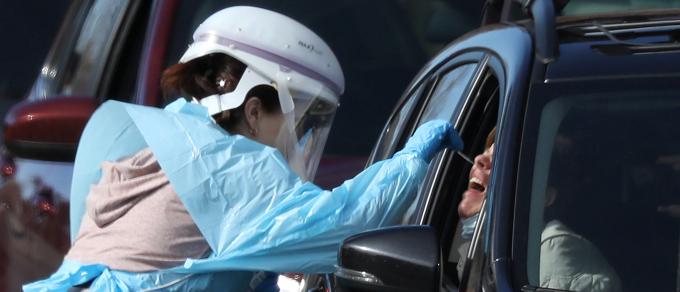 Health care worker tests people at a drive-thru testing station run by the state health department, for people who suspect they have novel coronavirus, in Denver