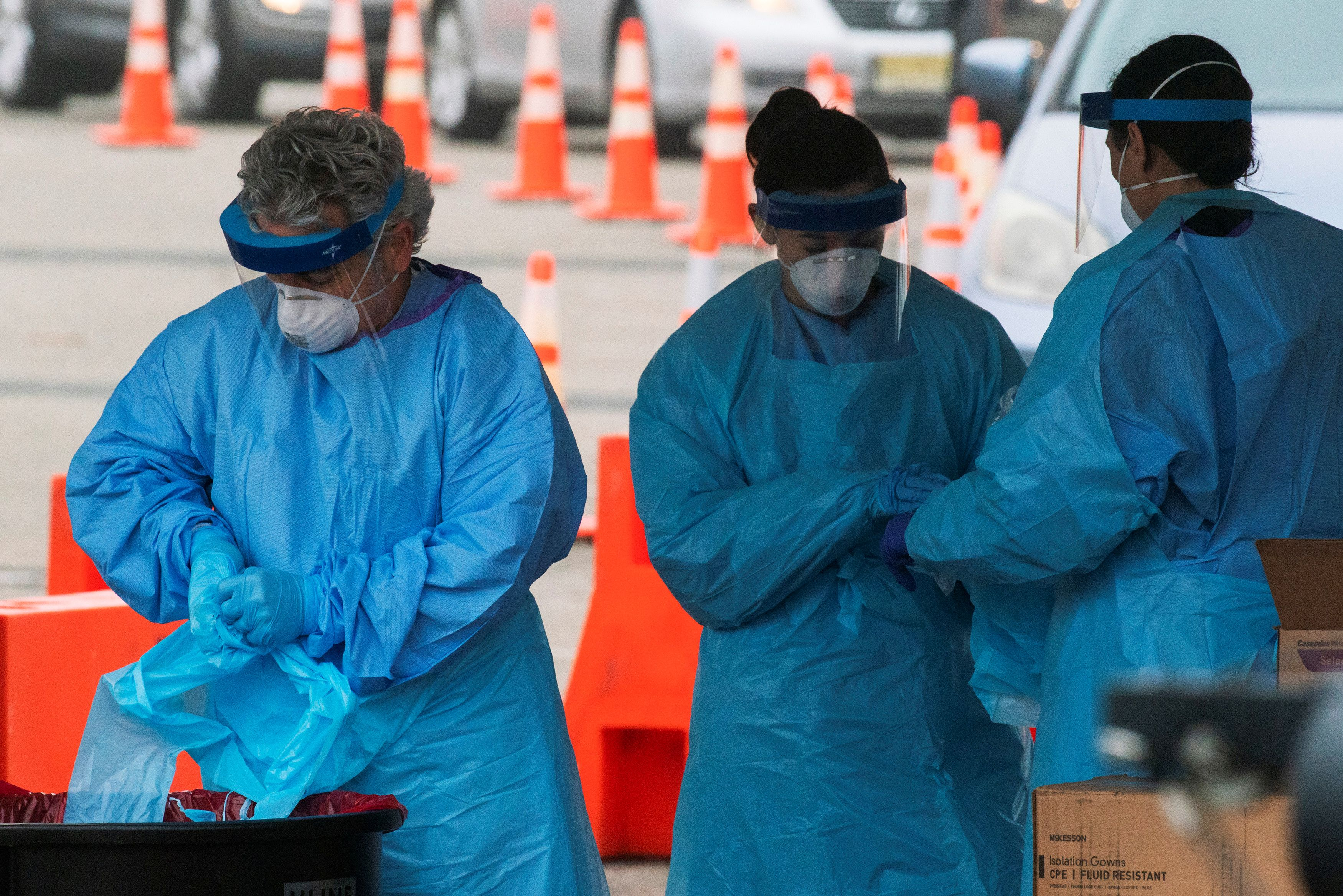 Health workers remove their gloves as they perform testing at a new drive-thru coronavirus disease (COVID-19) testing center at Bergen Community College in Paramus, New Jersey