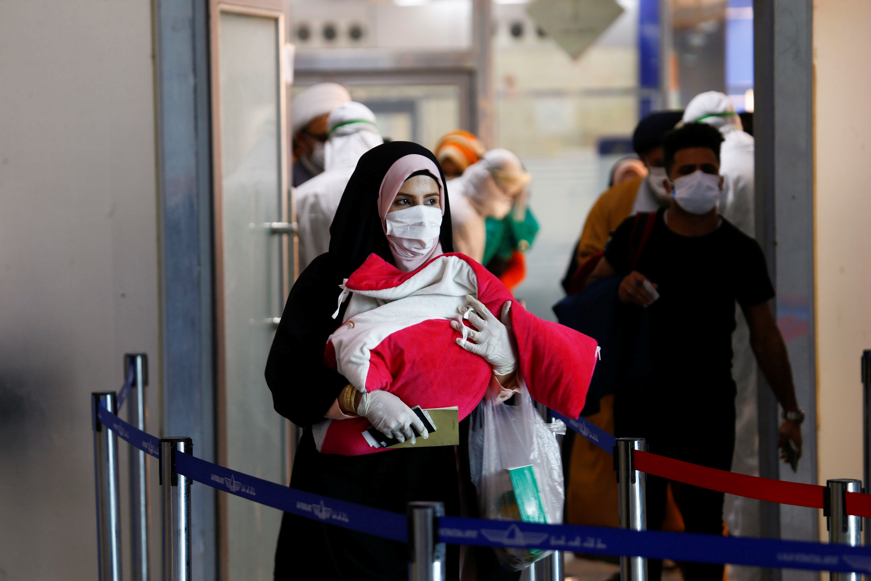 A woman wears a protective mask, as she carries her child amid concerns over the coronavirus (COVID-19) spread, at Najaf airport in the holy city of Najaf upon his arrival from Iran, Iraq March 15, 2020. REUTERS/Alaa al-marjan