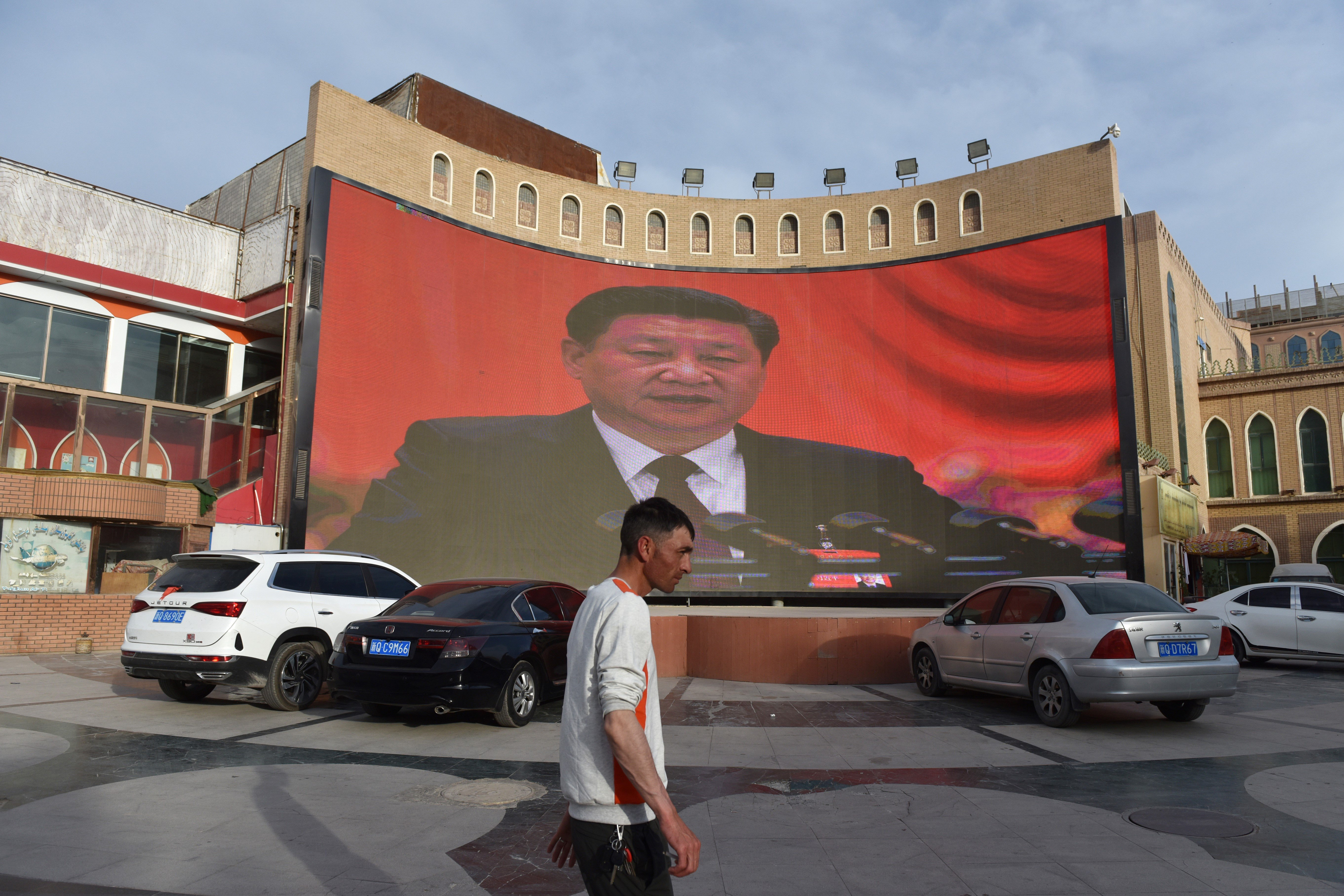 A man walking past a screen showing images of China's President Xi Jinping in Kashgar in China's northwest Xinjiang region (GREG BAKER/AFP via Getty Images)