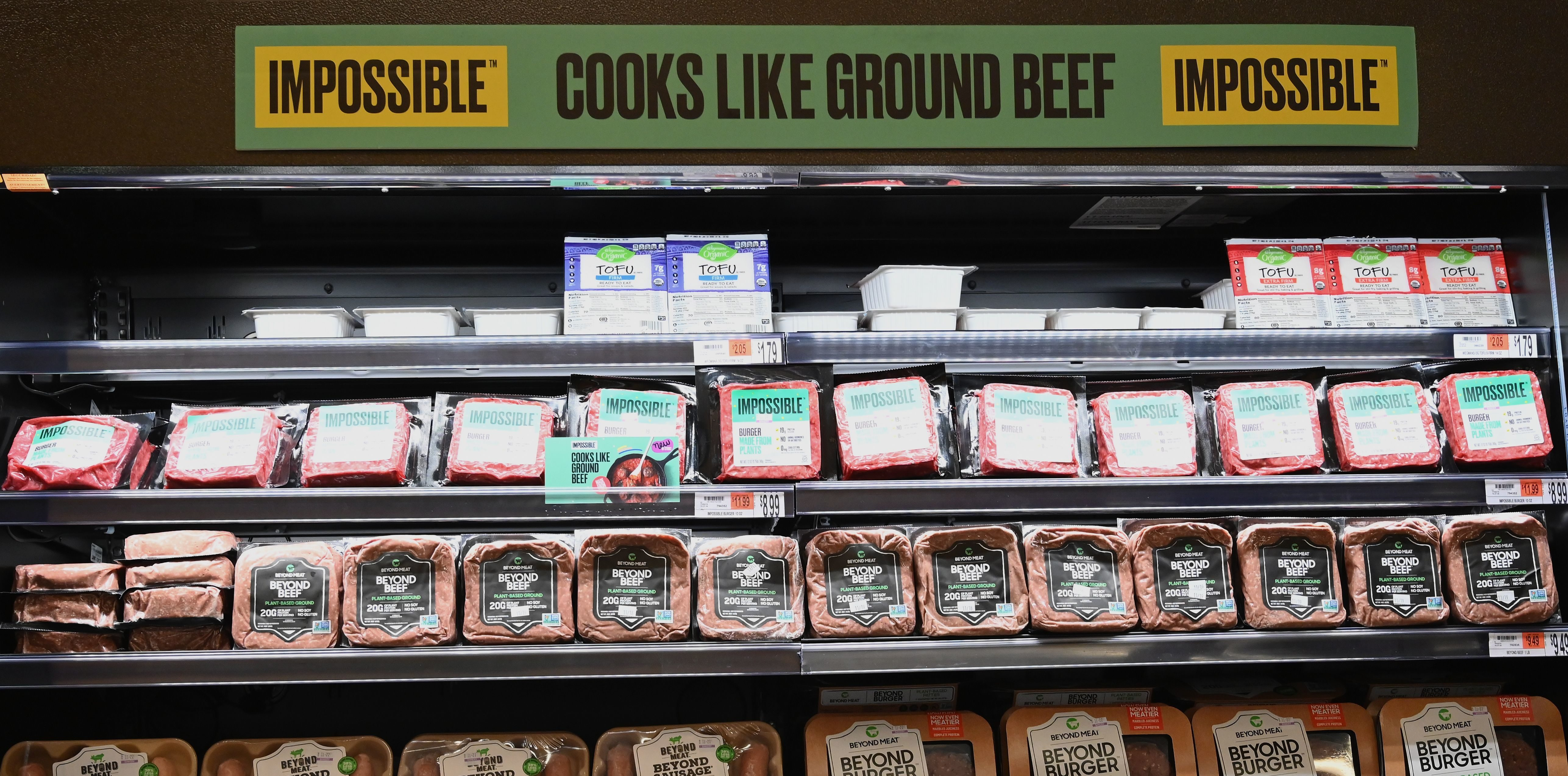 "Packages of ""Impossible Foods"" burgers and Beyond Meat made from plant-based substitutes for meat products sit on a shelf for sale on November 15, 2019 in New York City. -(Photo by ANGELA WEISS/AFP via Getty Images)"