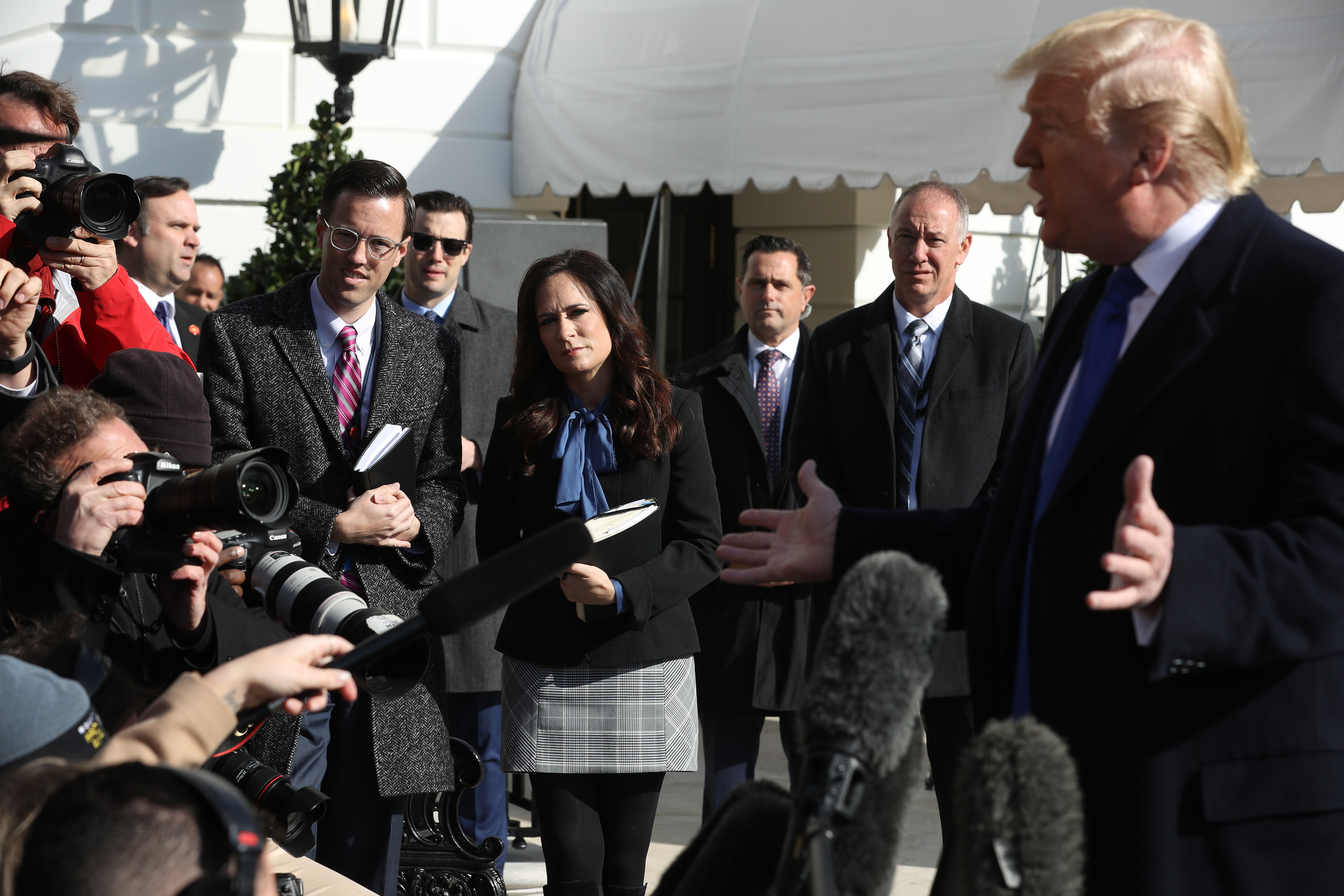 WASHINGTON, DC - NOVEMBER 08: White House Deputy Press Secretary Judd Deere and Press Secretary Stephanie Grisham (C) listen to U.S. President Donald Trump talk to reporters before he boards Marine One and departing the White House November 08, 2019 in Washington, DC. Trump is traveling to Atlanta, Georgia, where he plans to kick off his Black Voices for Trump Coalition, an effort to attract more African-American voters. (Photo by Chip Somodevilla/Getty Images)