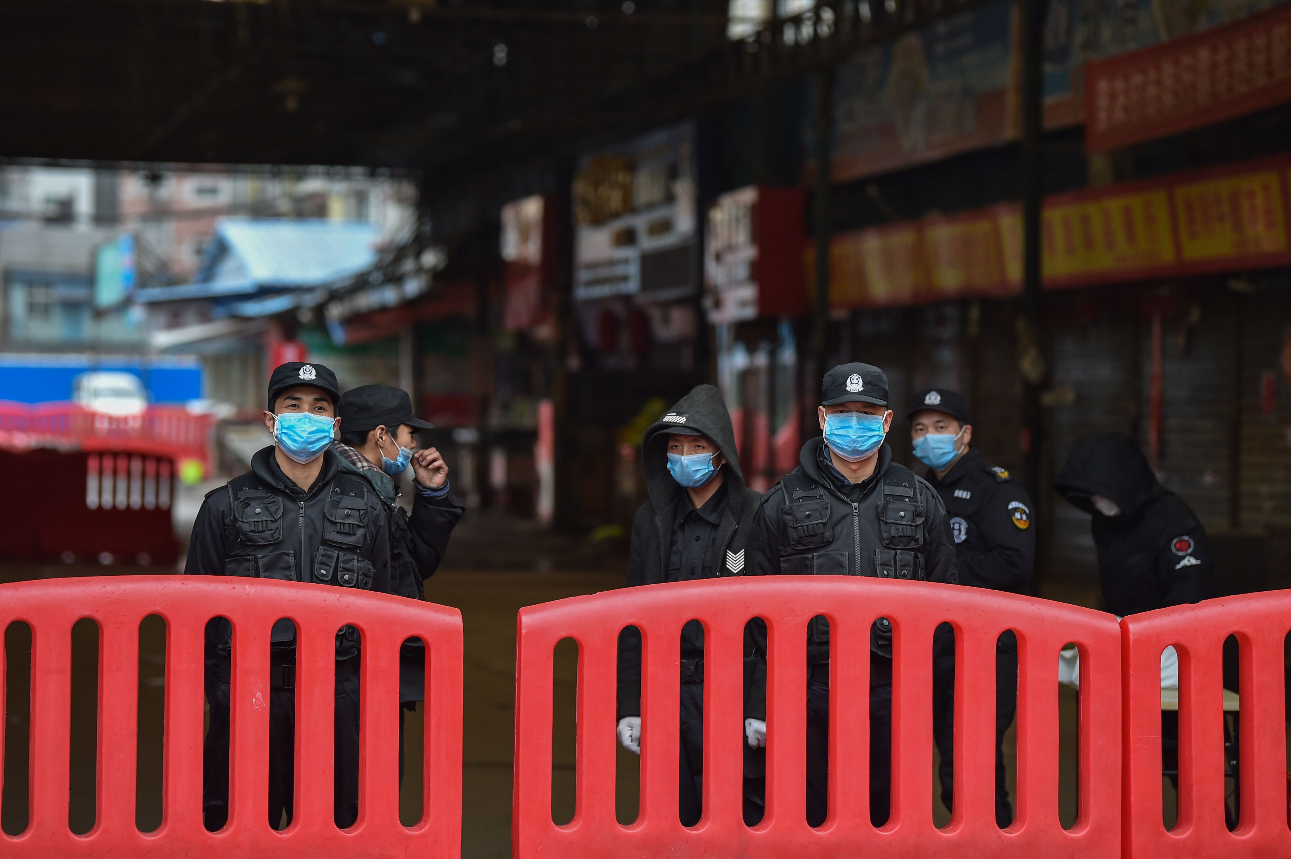A police officers and security guards stand outside the Huanan Seafood Wholesale Market where the coronavirus was detected in Wuhan on January 24, 2020. (HECTOR RETAMAL/AFP via Getty Images)