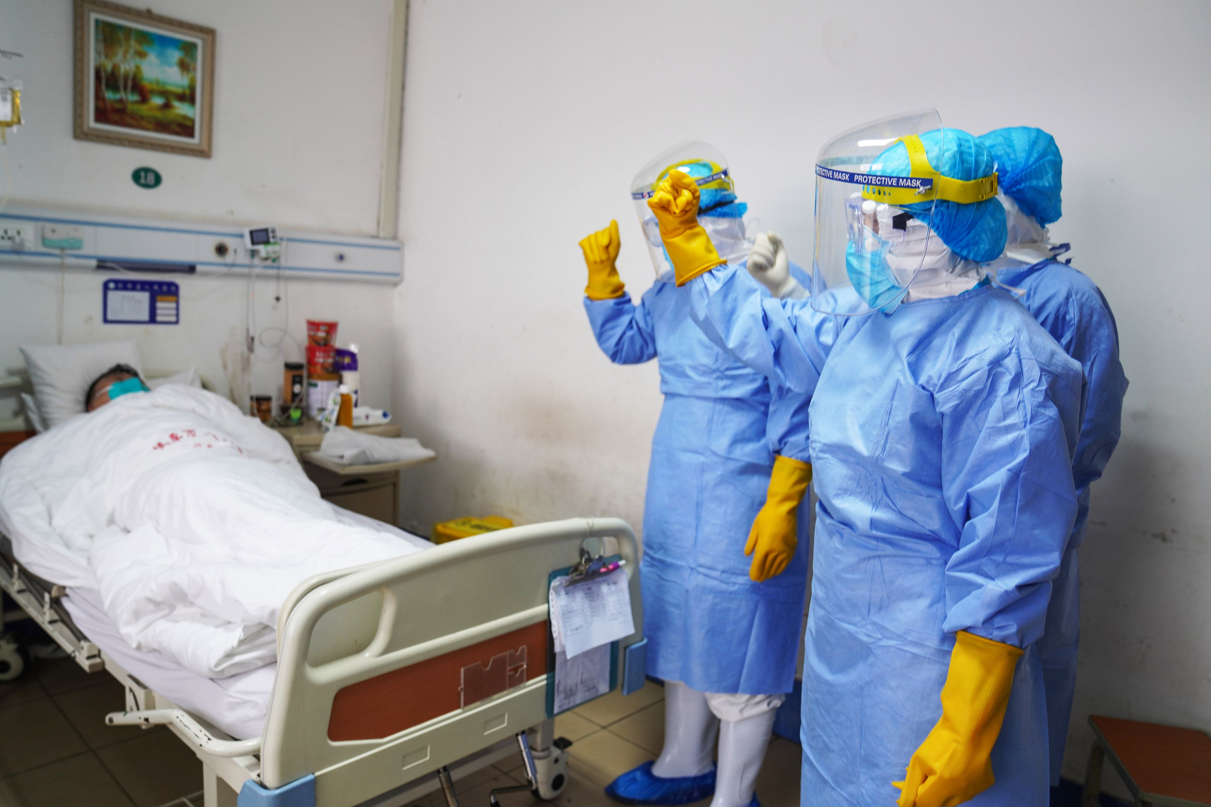 This photo taken on January 28, 2020 shows medical staff members cheering up a patient infected by the novel coronavirus in an isolation ward at a hospital in Zouping in China's easter Shandong province. - China faced deepening isolation over its coronavirus epidemic on February 1 as the death toll soared to 259, with the United States leading a growing list of nations to impose extraordinary Chinese travel bans. (Photo by STR / AFP) / China OUT (Photo by STR/AFP via Getty Images)
