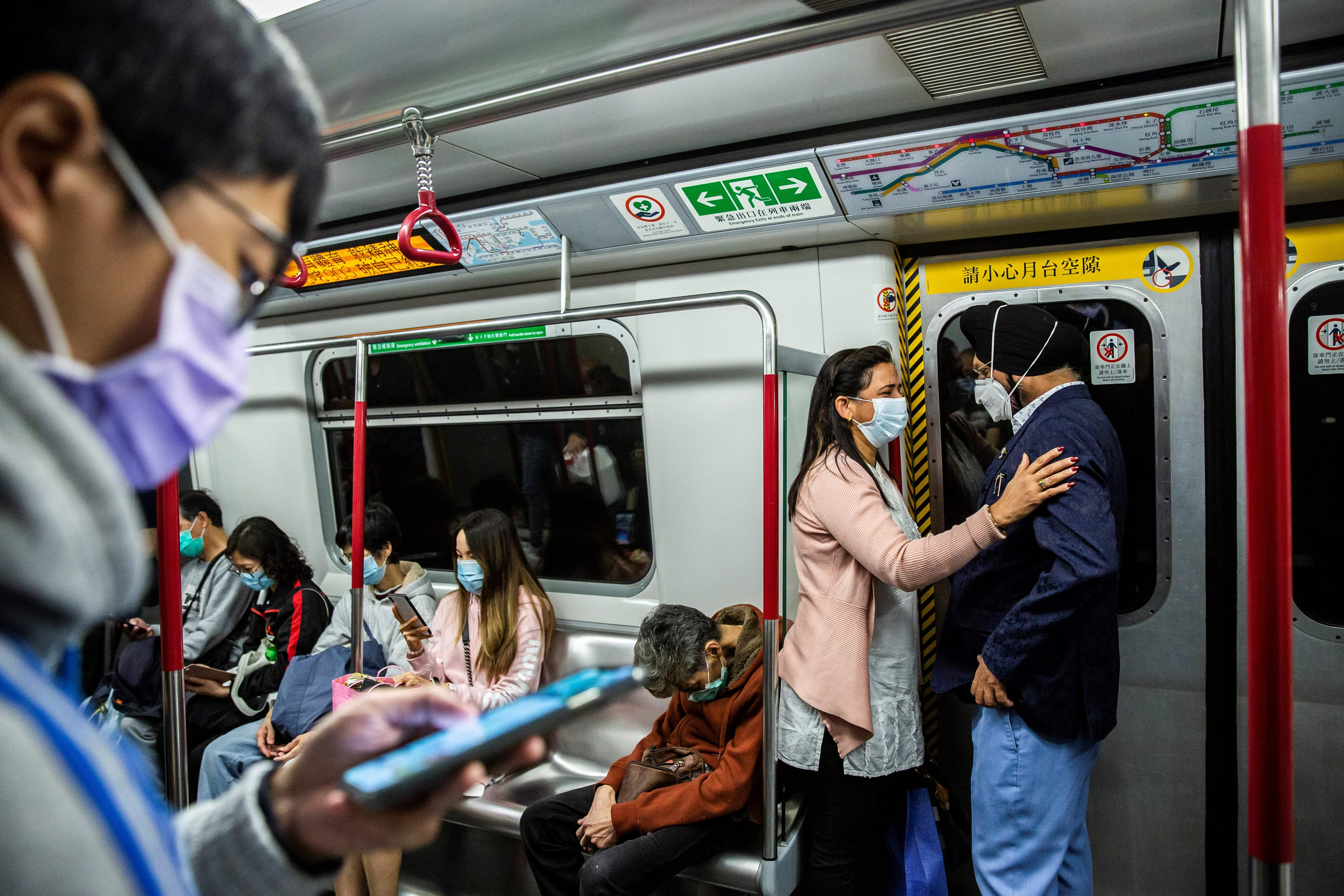 Passengers wearing protective face masks travel on the subway in Hong Kong on February 25, 2020. (ISAAC LAWRENCE/AFP via Getty Images)