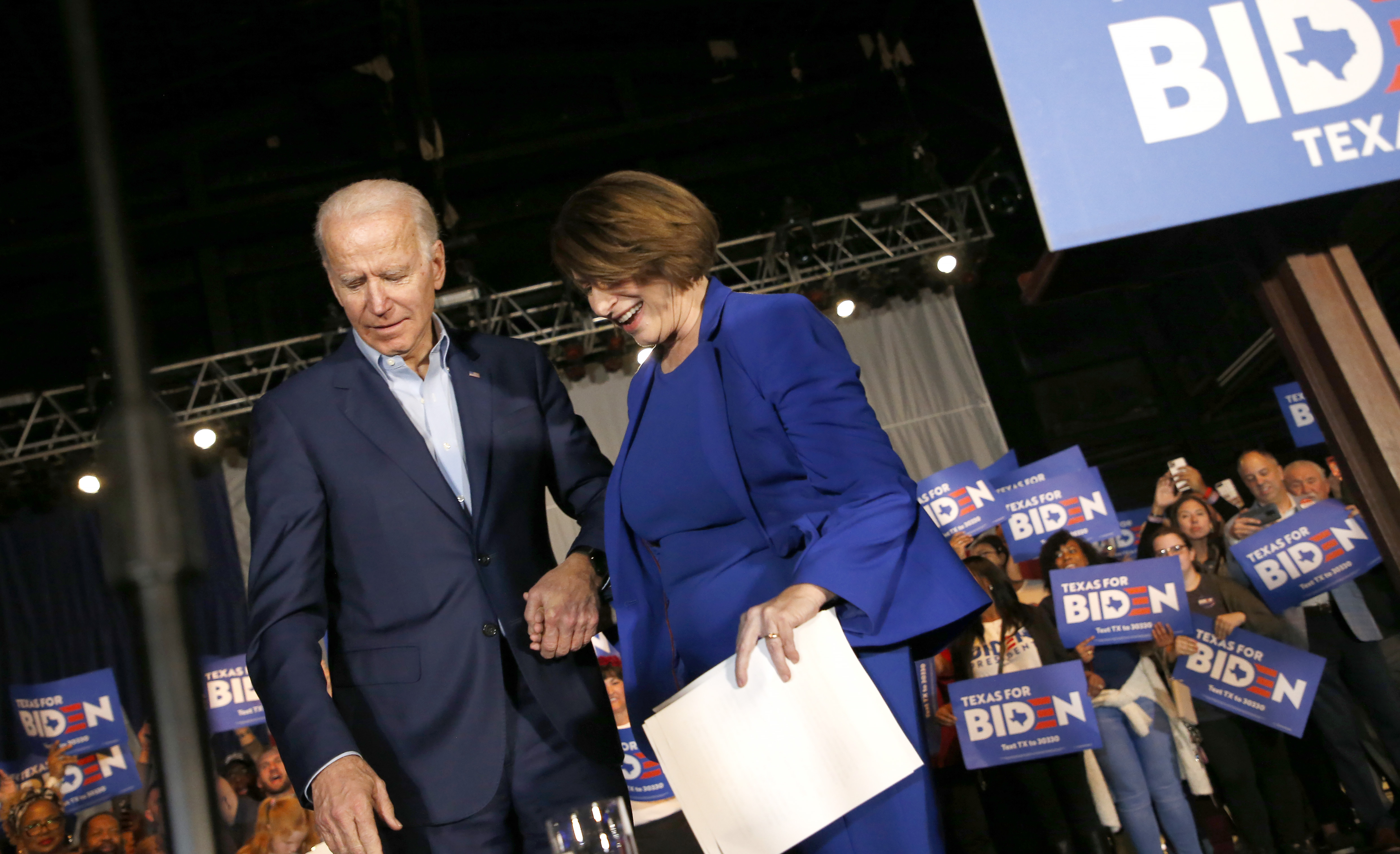 DALLAS, TX - MARCH 02: Democratic presidential candidate former Vice President Joe Biden helps Sen. Amy Klobuchar (D-MN) off the stage during a campaign event on March 2, 2020 in Dallas, Texas. Klobuchar has suspended her campaign and endorsed Biden before the upcoming Super Tuesday Democratic presidential primaries. (Photo by Ron Jenkins/Getty Images)