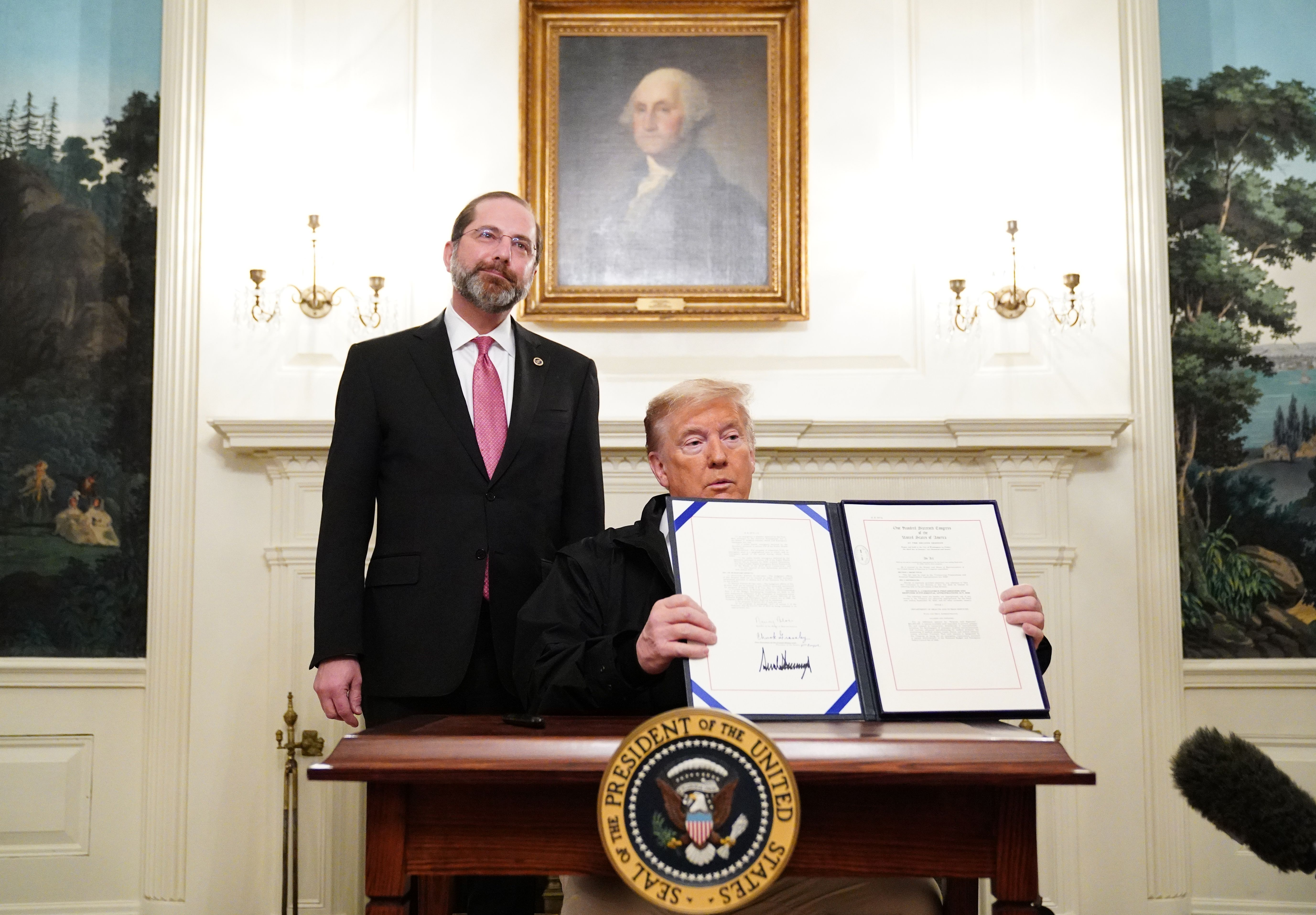 US President Donald Trump holds up an USD 8 billion emergency funding bill to combat COVID-19, coronavirus, after signing it as US Health Secretary Alex Azar looks on in the Diplomatic Room of the White House in Washington, DC on March 6, 2020. (Photo by MANDEL NGAN/AFP via Getty Images)