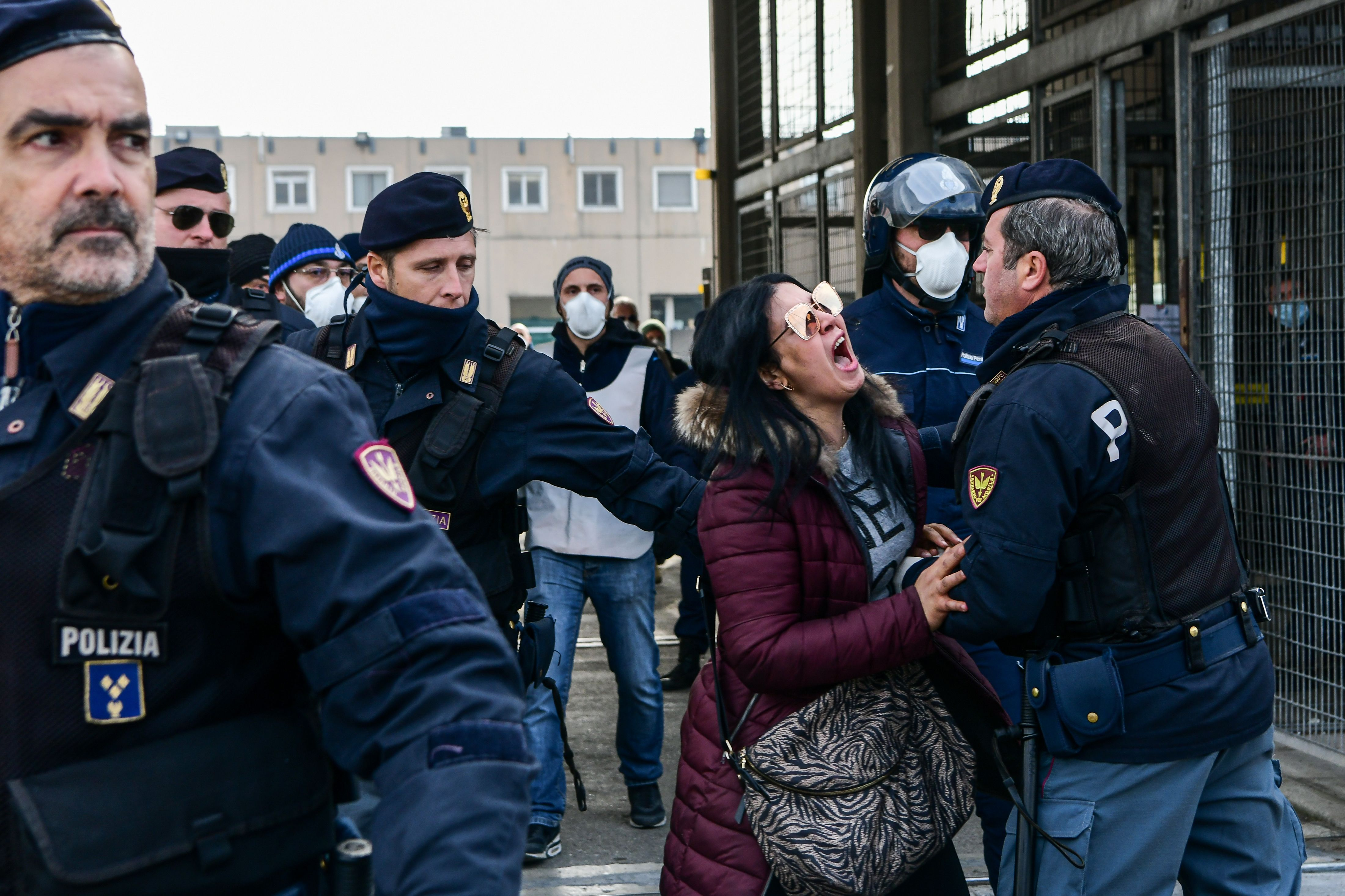 Police officers hold off an inmate's relative shouting in protest outside the SantAnna prison in Modena, Emilia-Romagna, in one of Italy's quarantine red zones on March 9, 2020. (PIERO CRUCIATTI/AFP via Getty Images)