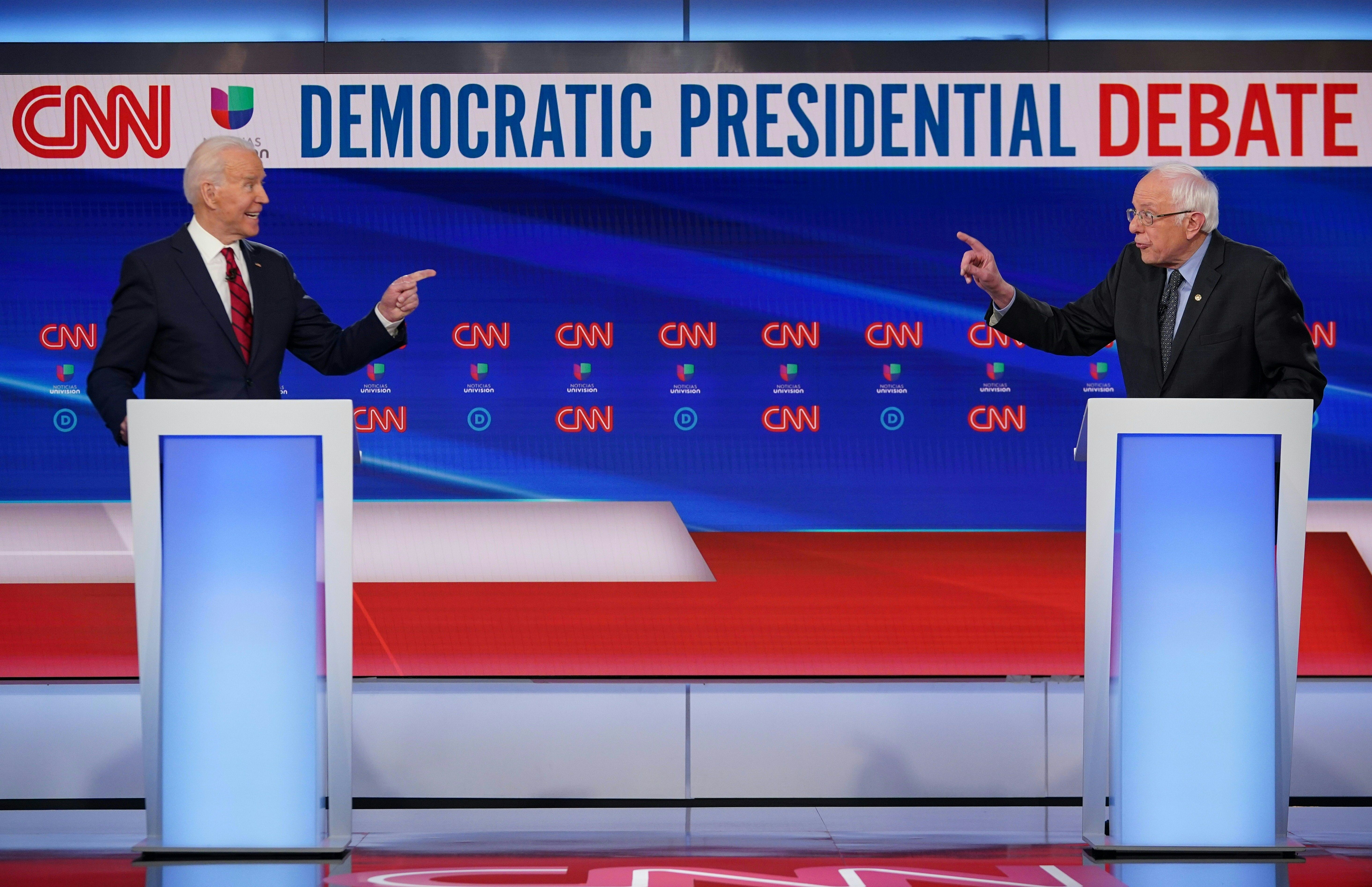 Democratic presidential hopefuls former US vice president Joe Biden (L) and Senator Bernie Sanders point fingers at each other as they take part in the 11th Democratic Party 2020 presidential debate in a CNN Washington Bureau studio in Washington, DC on March 15, 2020. (MANDEL NGAN/AFP via Getty Images)