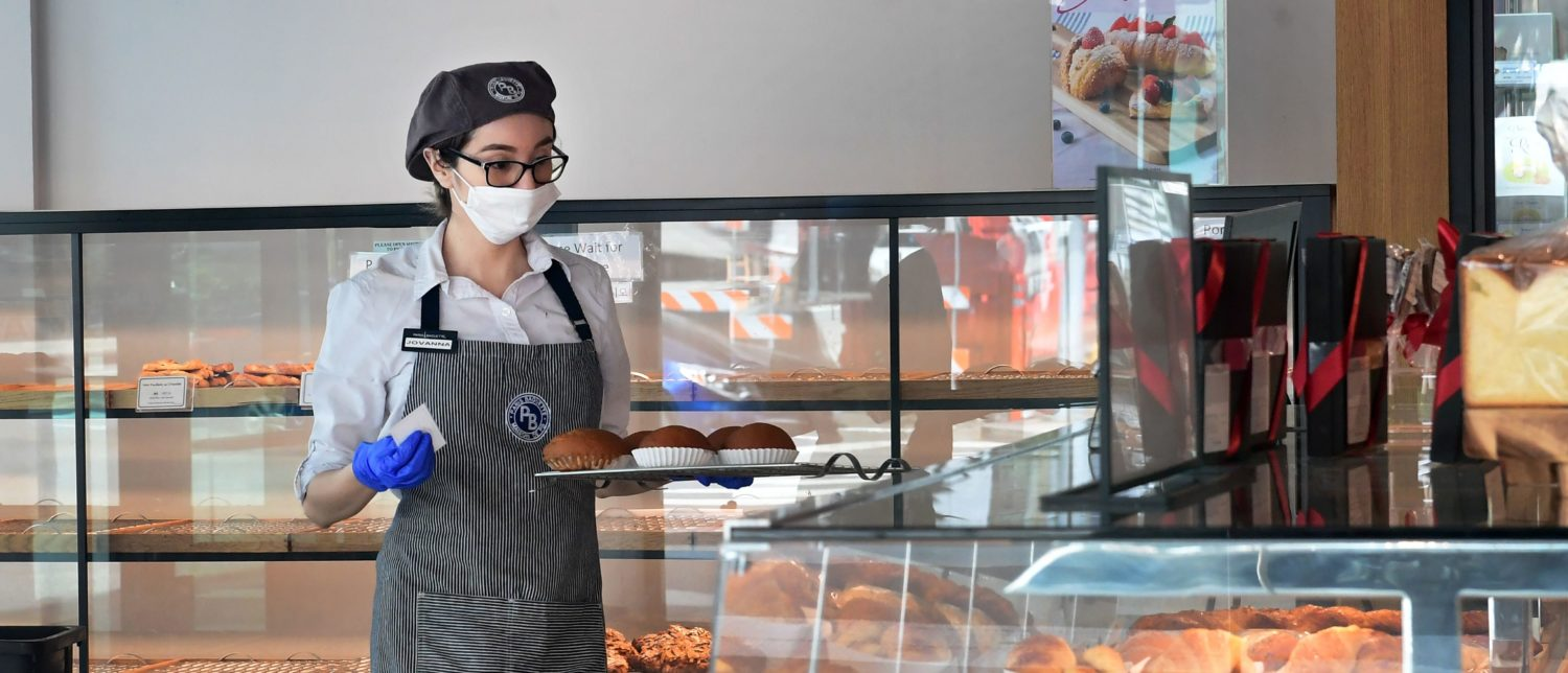 An employee at a Cafe and Bakery wears a facemask in Los Angeles, California on March 17, 2020 as the coronavirus (covid-19) epidemic leads to restaurant and school closures as workers work from home in an effort to encourage distancing. (FREDERIC J. BROWN/AFP via Getty Images)