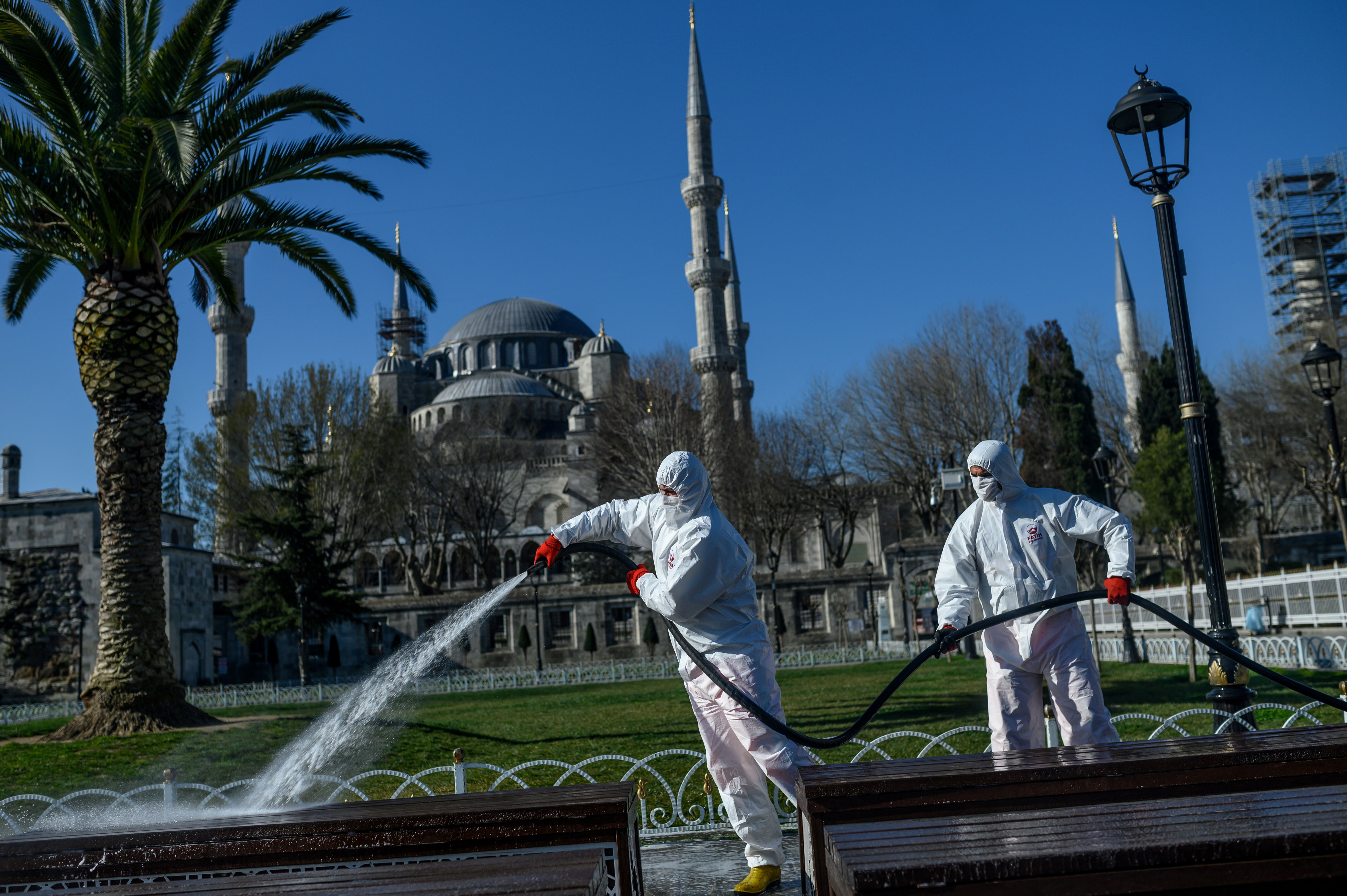 Members of the Fatih Municipality disinfect and wash down the Sultanahmet Square in front of the Blue Mosque in Istanbul to prevent the spread of the novel coronavirus. (BULENT KILIC/AFP via Getty Images)
