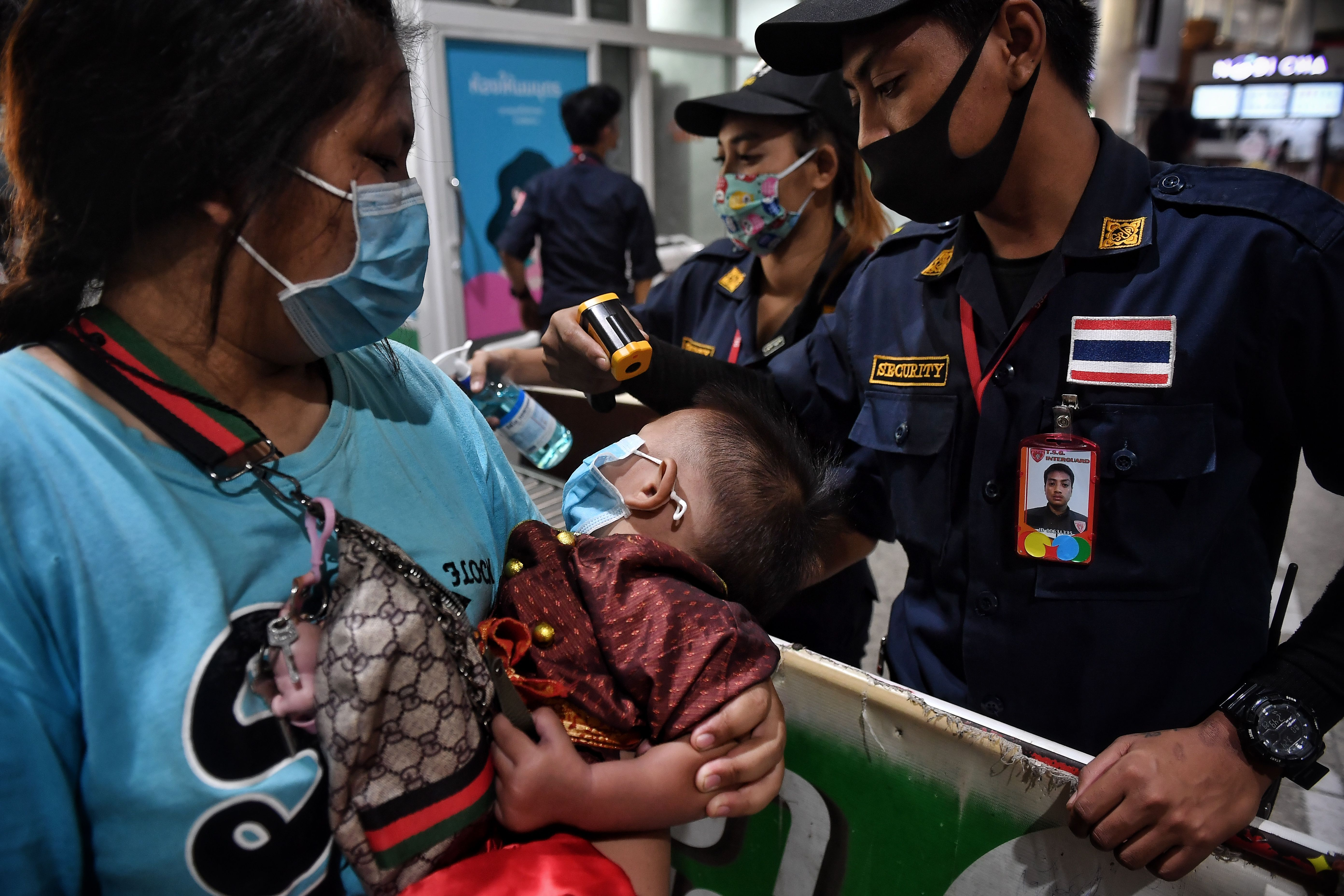 Officials check the temperature of an infant as thousands of migrant workers try to leave the Thai capital for their home provinces amid concerns over the spread of the COVID-19 coronavirus, at Mo Chit Bus Terminal in Bangkok on March 23, 2020. - (Photo by LILLIAN SUWANRUMPHA/AFP via Getty Images)