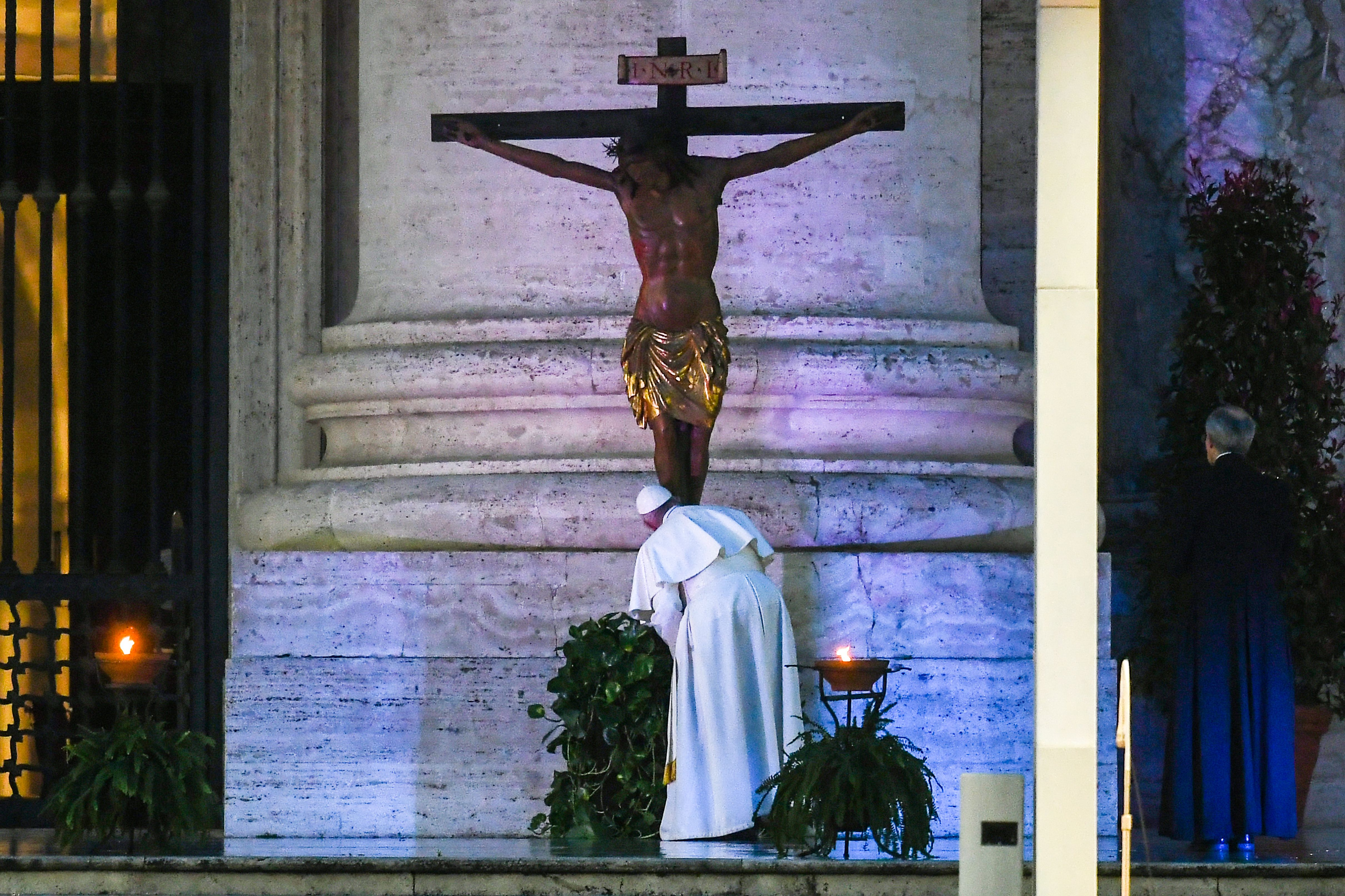 Pope Francis kisses a miraculous crucifix that in 1552 was carried in a procession around Rome to stop the great plague, (Photo by VINCENZO PINTO/AFP via Getty Images)