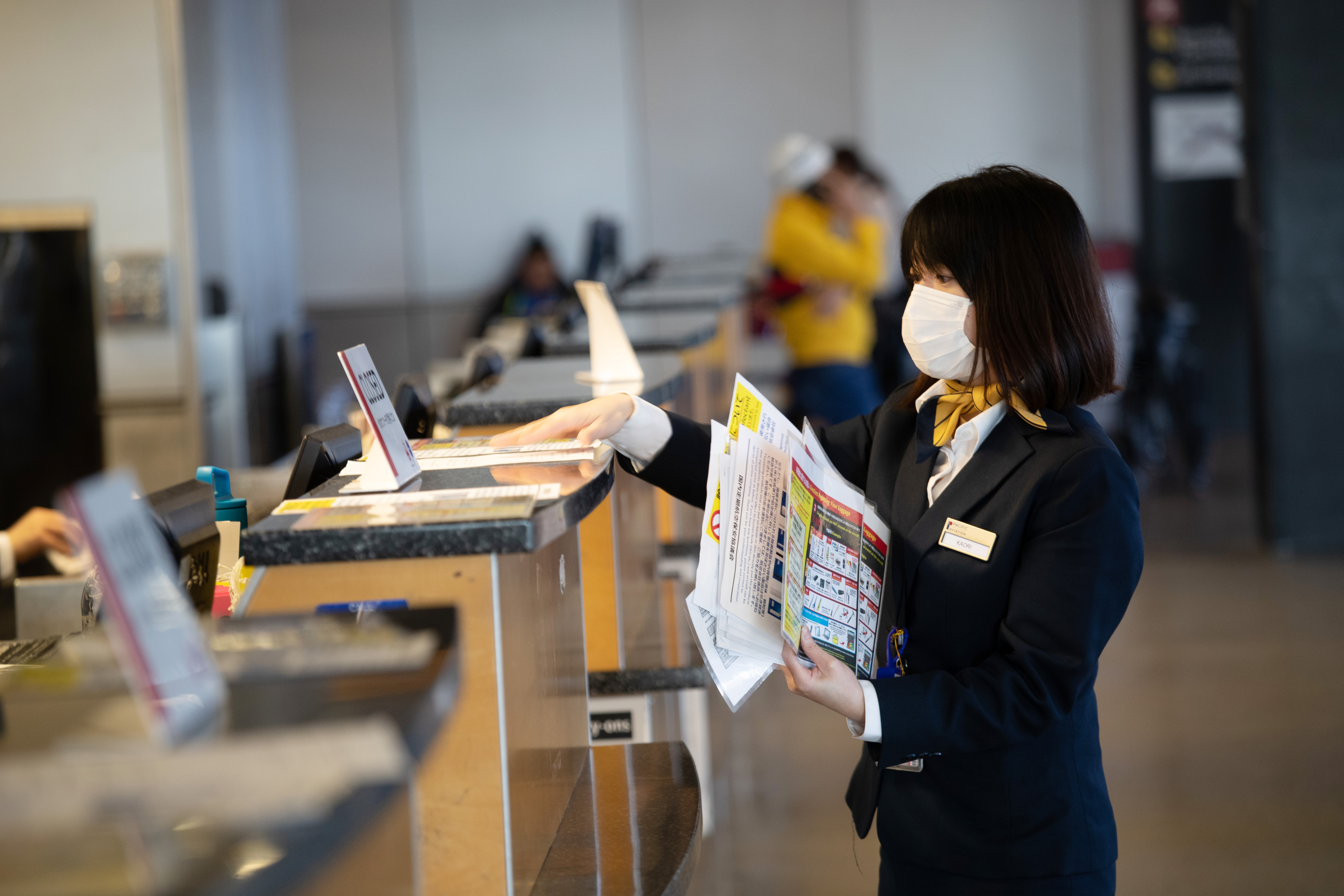 An airline employee places literature at check-in counters at the Seattle-Tacoma International Airport on March 15, 2020 in Seattle, Washington. (John Moore/Getty Images)