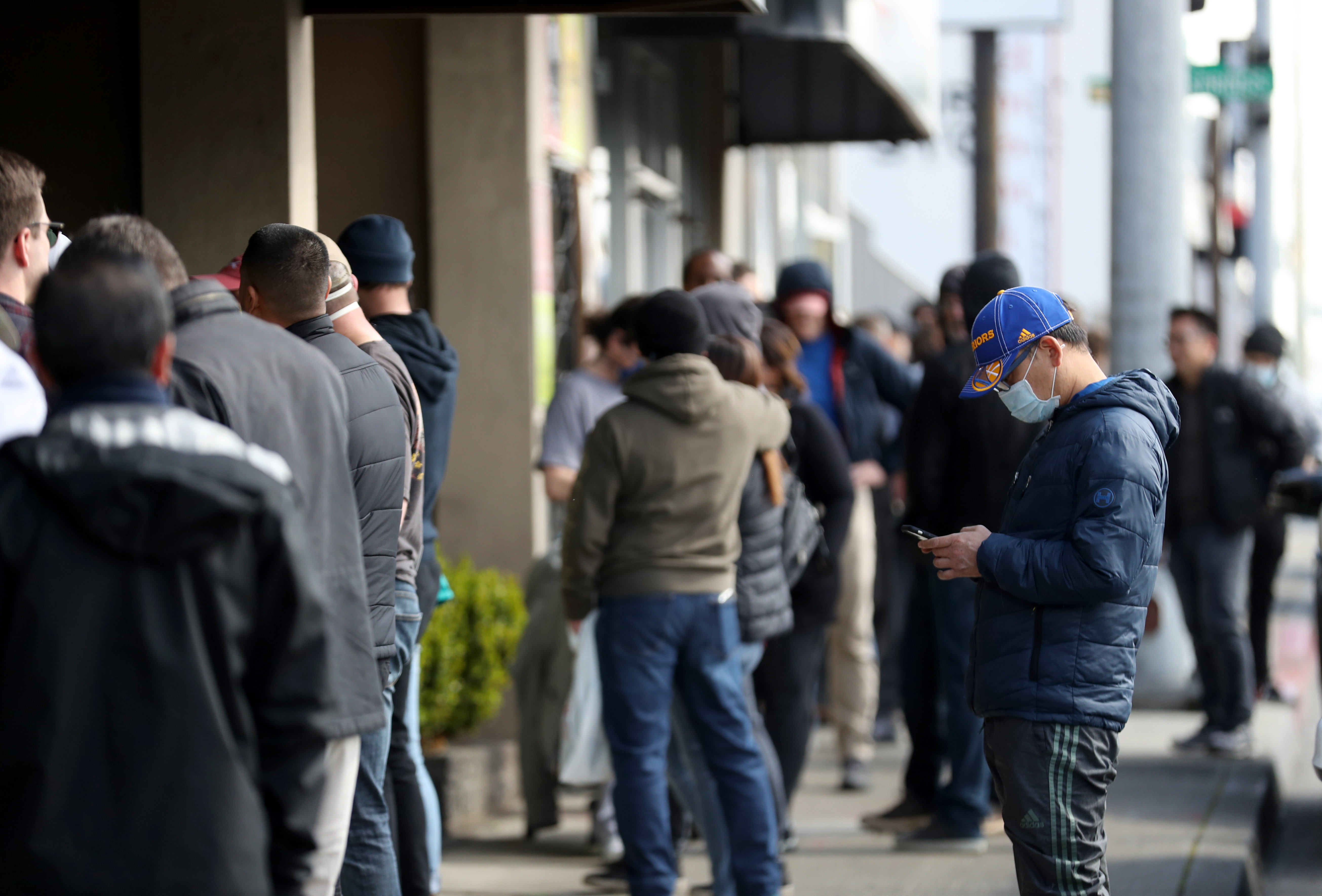 People wait in line to purchase guns and ammunition at Peninsula Guns and Tactical on March 16, 2020 in San Bruno, California. (Justin Sullivan/Getty Images)