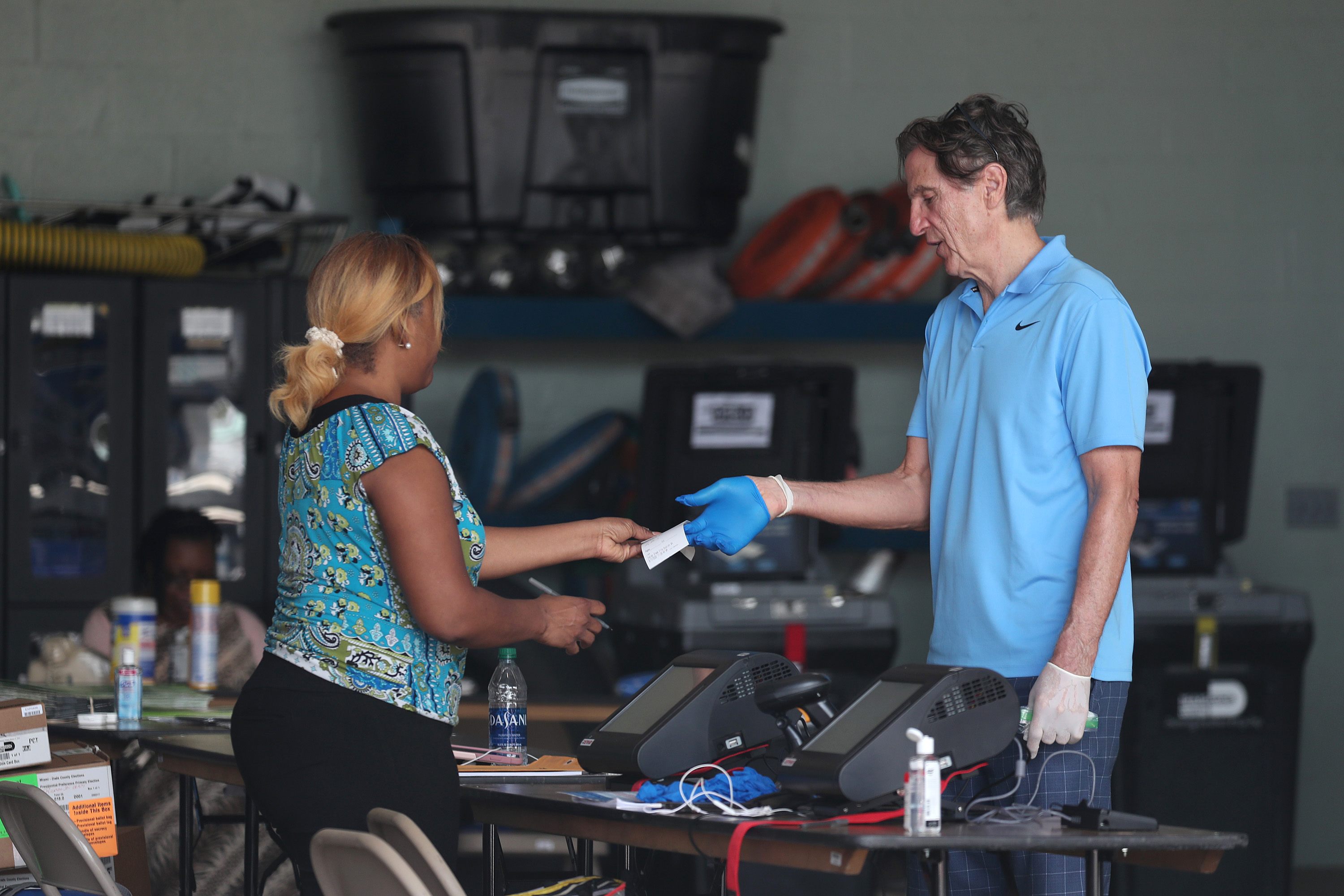 A poll worker checks in George Hanley, who is wearing protective gloves, as he prepares to cast a ballot in his precinct setup in Miami Beach Fire Station 4 during the Florida presidential primary as the coronavirus pandemic continues on March 17, 2020 in Miami Beach, Florida. (Joe Raedle/Getty Images)