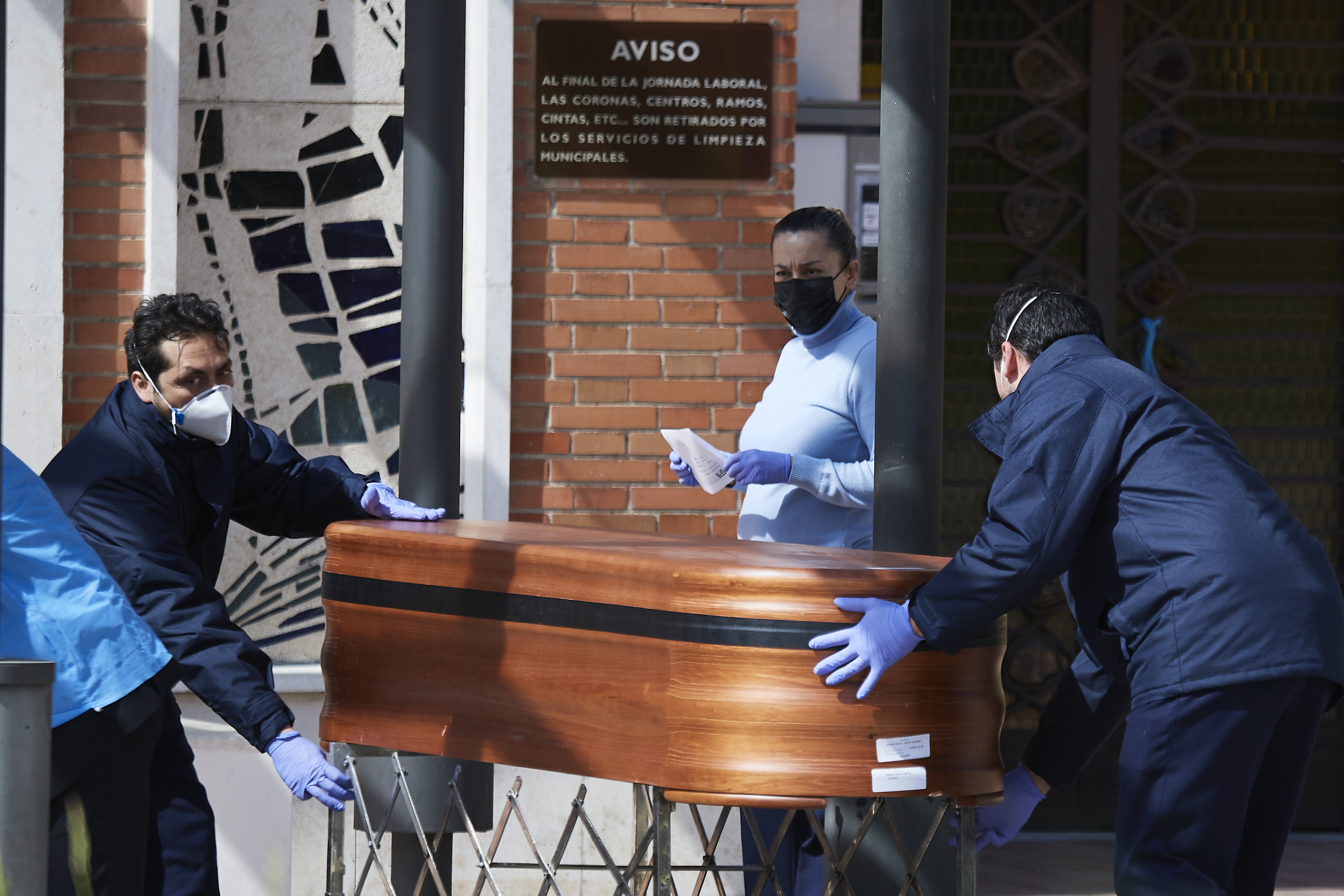 MADRID, SPAIN - MARCH 26: Two workers transport a coffin at La Almudena cemetery on March 26, 2020 in Madrid, Spain. Spain plans to continue its quarantine measures at least through April 11. The Coronavirus (COVID-19) pandemic has spread to many countries across the world, claiming over 20,000 lives and infecting hundreds of thousands more. (Photo by Carlos Alvarez/Getty Images)