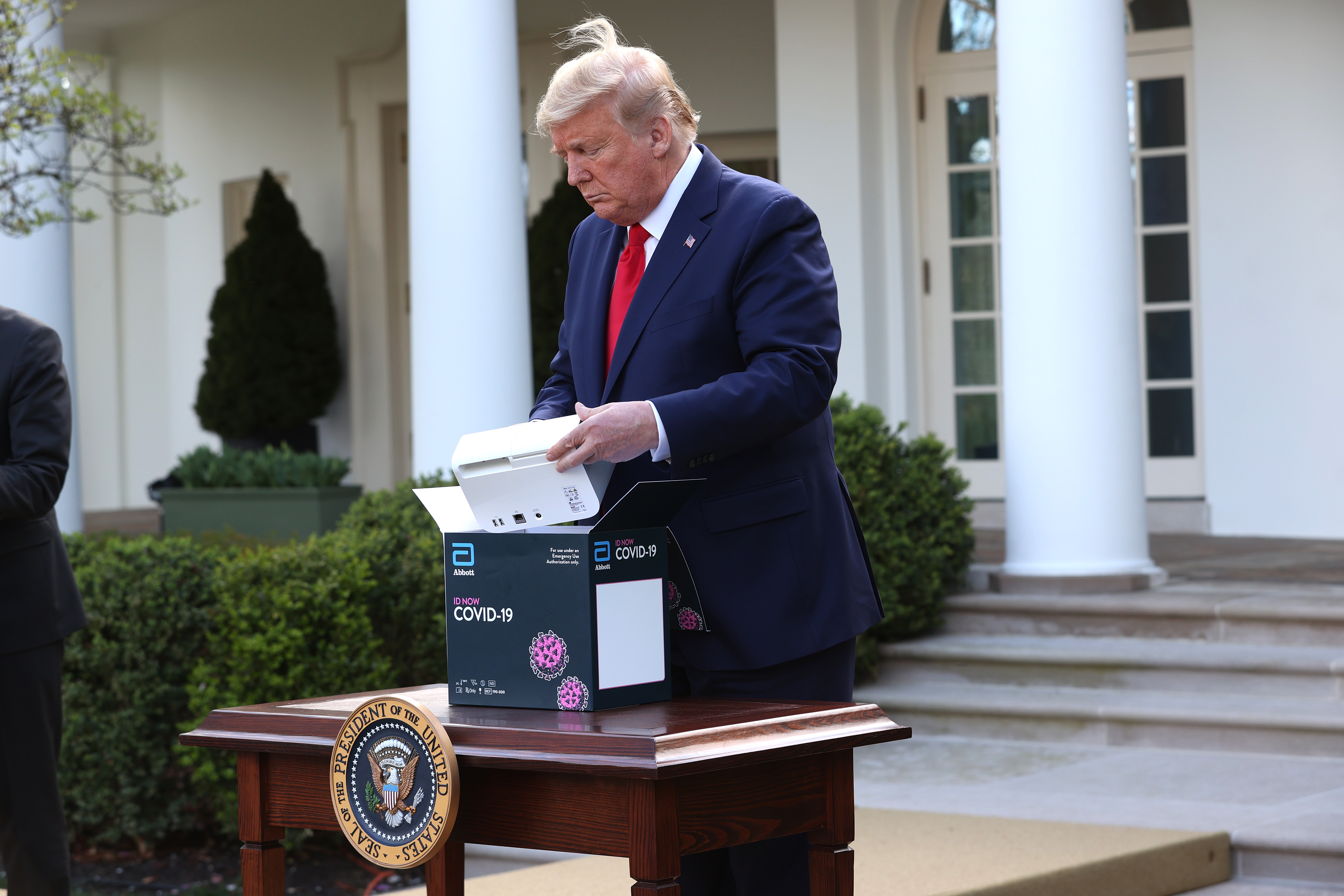 WASHINGTON, DC - MARCH 30: U.S. President Donald Trump takes a new COVID-19 test kit developed by Abbott Labs out of its box during the daily coronavirus briefing at the Rose Garden of the White House on March 30, 2020 in Washington, DC. The United States has updated its guidelines to U.S. citizens to maintain current social distancing practices through the end of April after the number of reported coronavirus (COVID-19) deaths doubled to over 2,000 nationwide within two days. (Photo by Win McNamee/Getty Images)