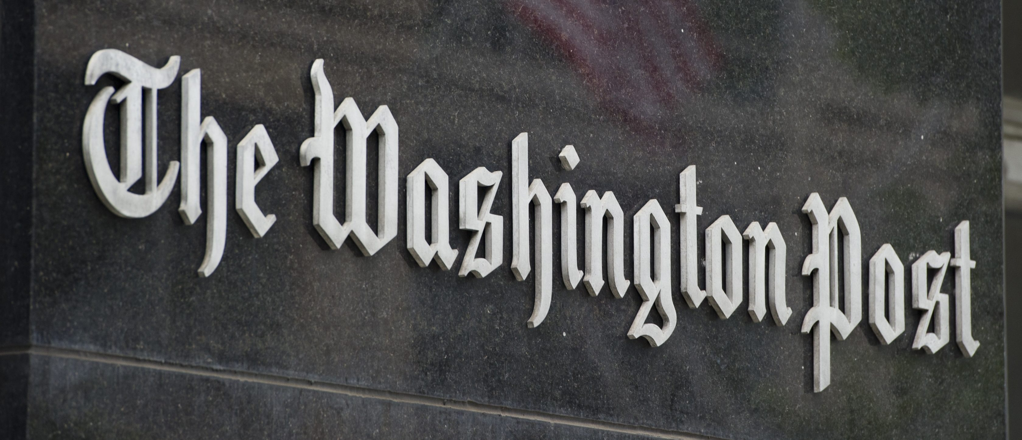 A sign hangs on the outside of the Washington Post Building August 6, 2013 in Washington, DC, the day after it was announced that Amazon.com founder and CEO Jeff Bezos had agreed to purchase the newspaper for USD 250 million. (SAUL LOEB/AFP via Getty Images)