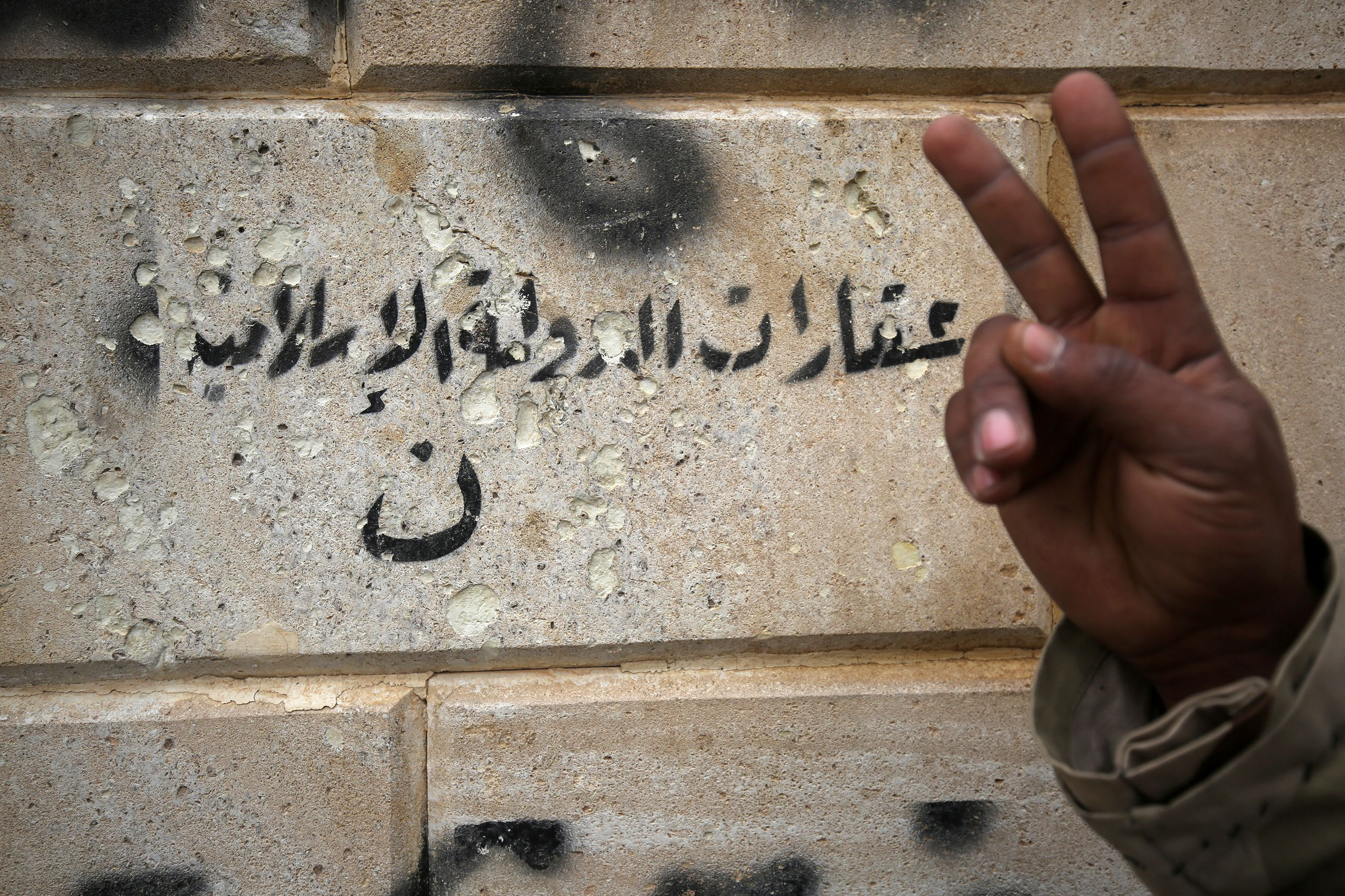 "An Iraqi soldier gestures next to an Islamic State (IS) group graffiti bearing letter ""N"" in Arabic, which stands for Christian (AHMAD AL-RUBAYE/AFP via Getty Images)"