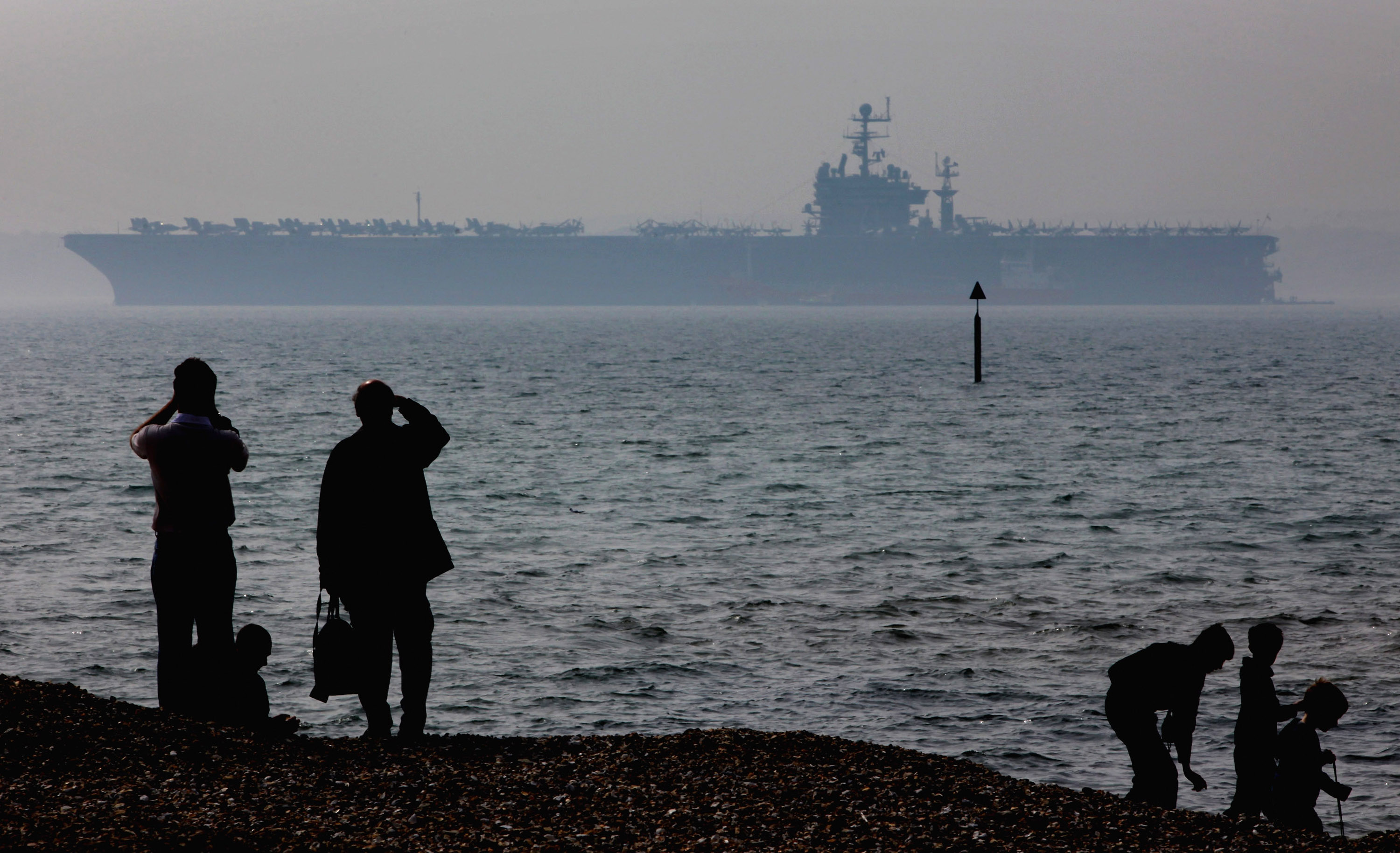 People stop to look at the USS Theodore Roosevelt anchored off Stokes Bay on April 6, 2009 in Portsmouth, England. (Matt Cardy/Getty Images)