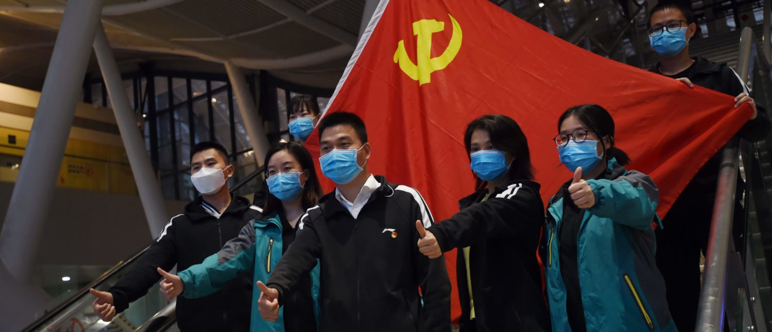 Medical workers from outside Wuhan pose for pictures with a Chinese Communist Party flag at the Wuhan Railway Station before leaving the epicentre of the novel coronavirus disease (COVID-19) outbreak, in Hubei province, China March 17, 2020. Picture taken March 17, 2020. REUTERS/Stringer