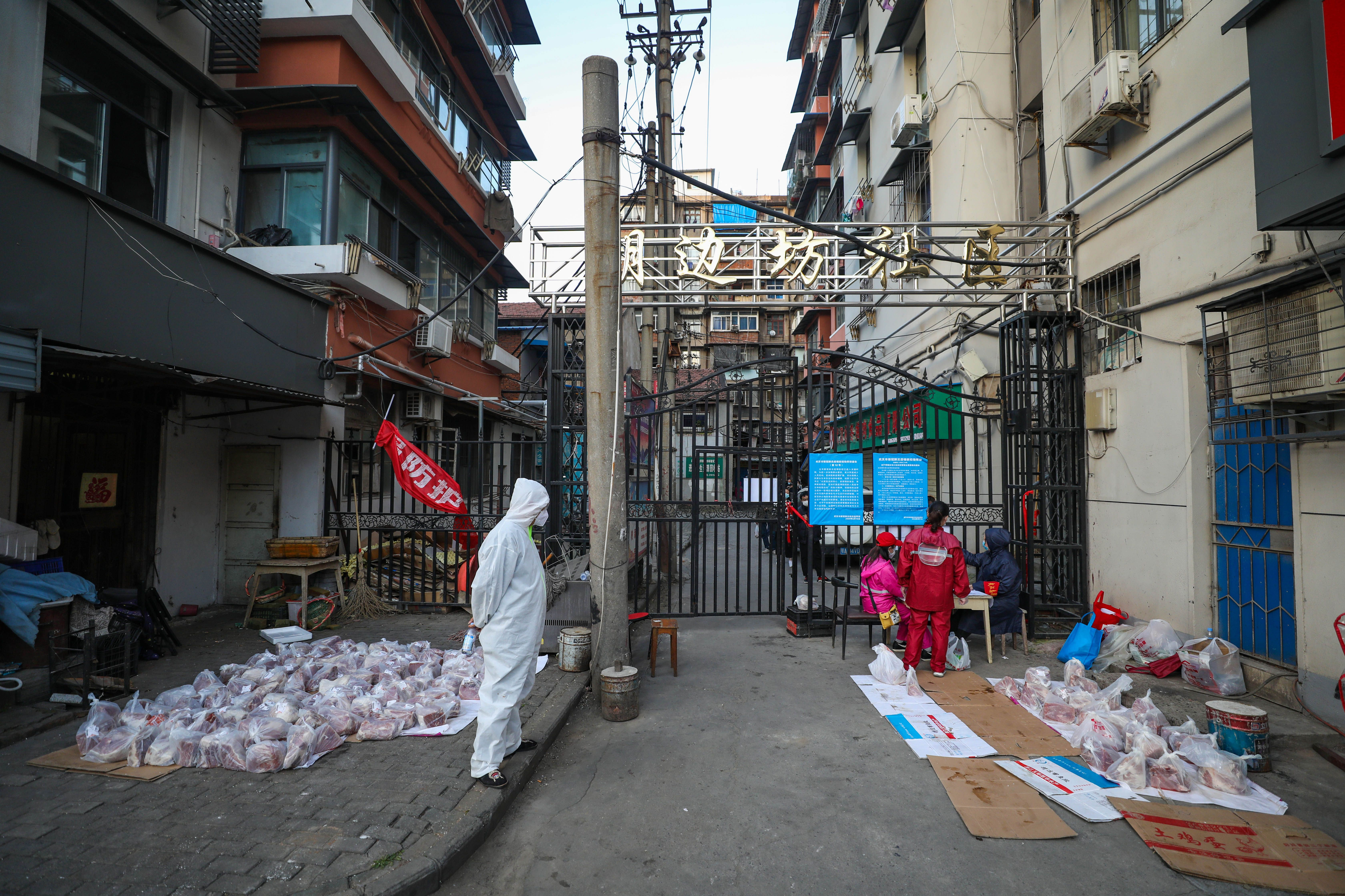 This photo taken on March 18, 2020 shows a volunteer wearing a protective suit as he watches over a delivery of pork for quarantined residents in Wuhan, in China's central Hubei province. (Photo by STR/AFP via Getty Images)