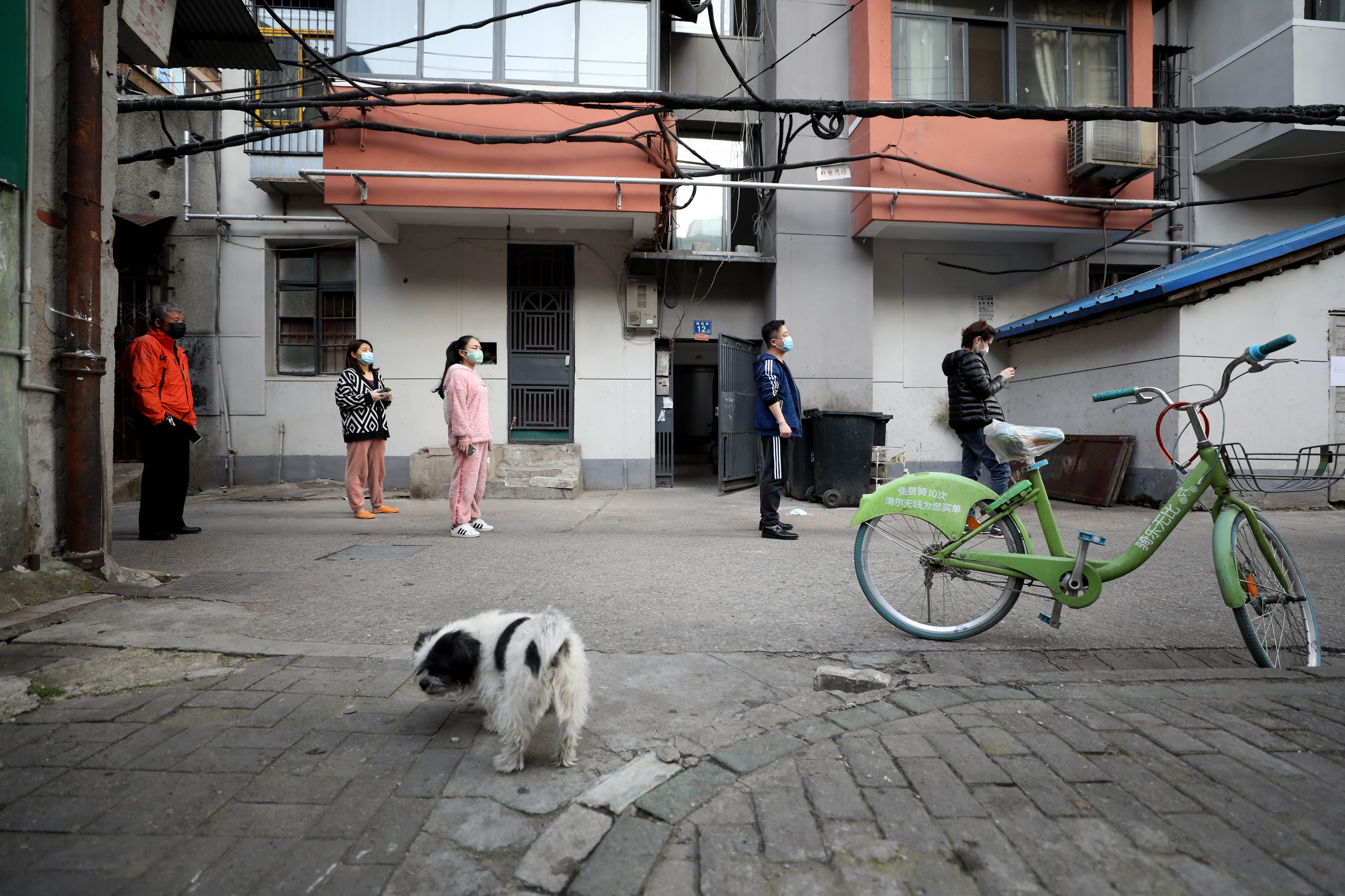 This photo taken on March 18, 2020 shows residents lining up to pick up food which was delivered to their quarantined compound in Wuhan, in China's central Hubei province. (Photo by STR/AFP via Getty Images)