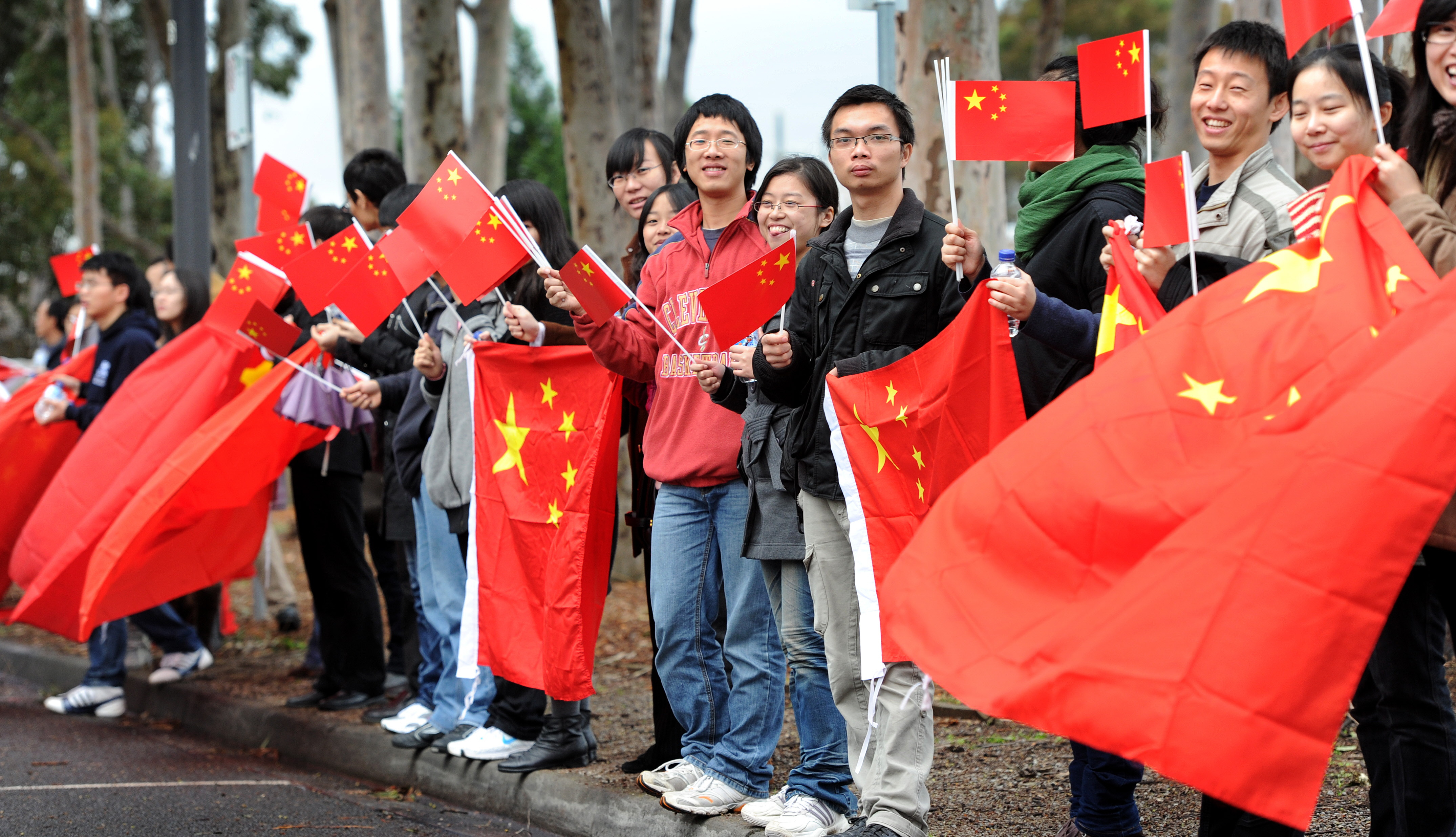 Chinese consular staff wave national flags in front of a demonstration by supporters of the Falungong spiritual movement outside the venue where China's Vice President Xi Jinping was opening Australia's first Chinese Medicine Confucius Institute. ( WILLIAM WEST/AFP via Getty Images)