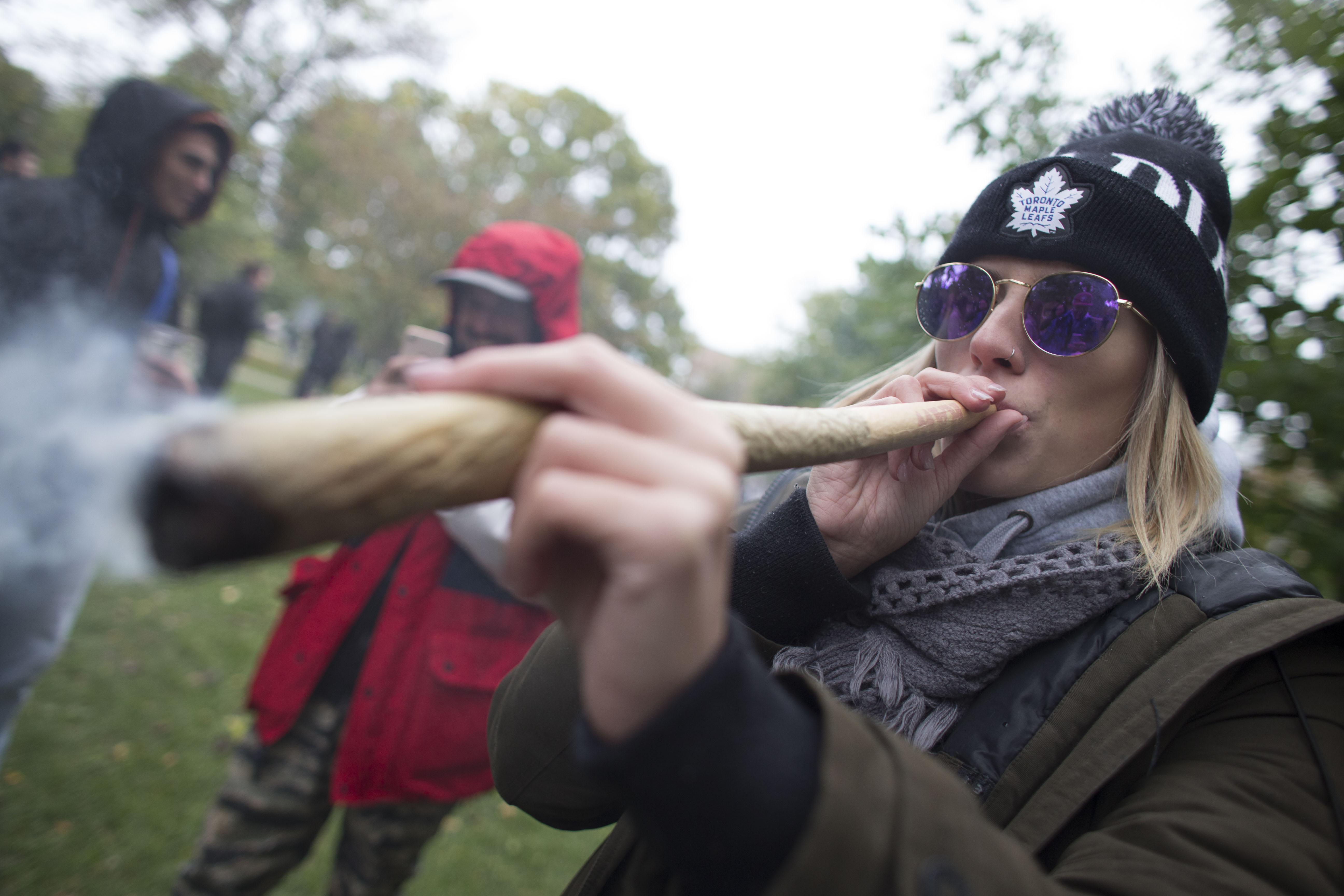 A woman smokes a marijuana cigarette during a legalization party at Trinity Bellwoods Park in Toronto, Ontario. (GEOFF ROBINS/AFP via Getty Images)