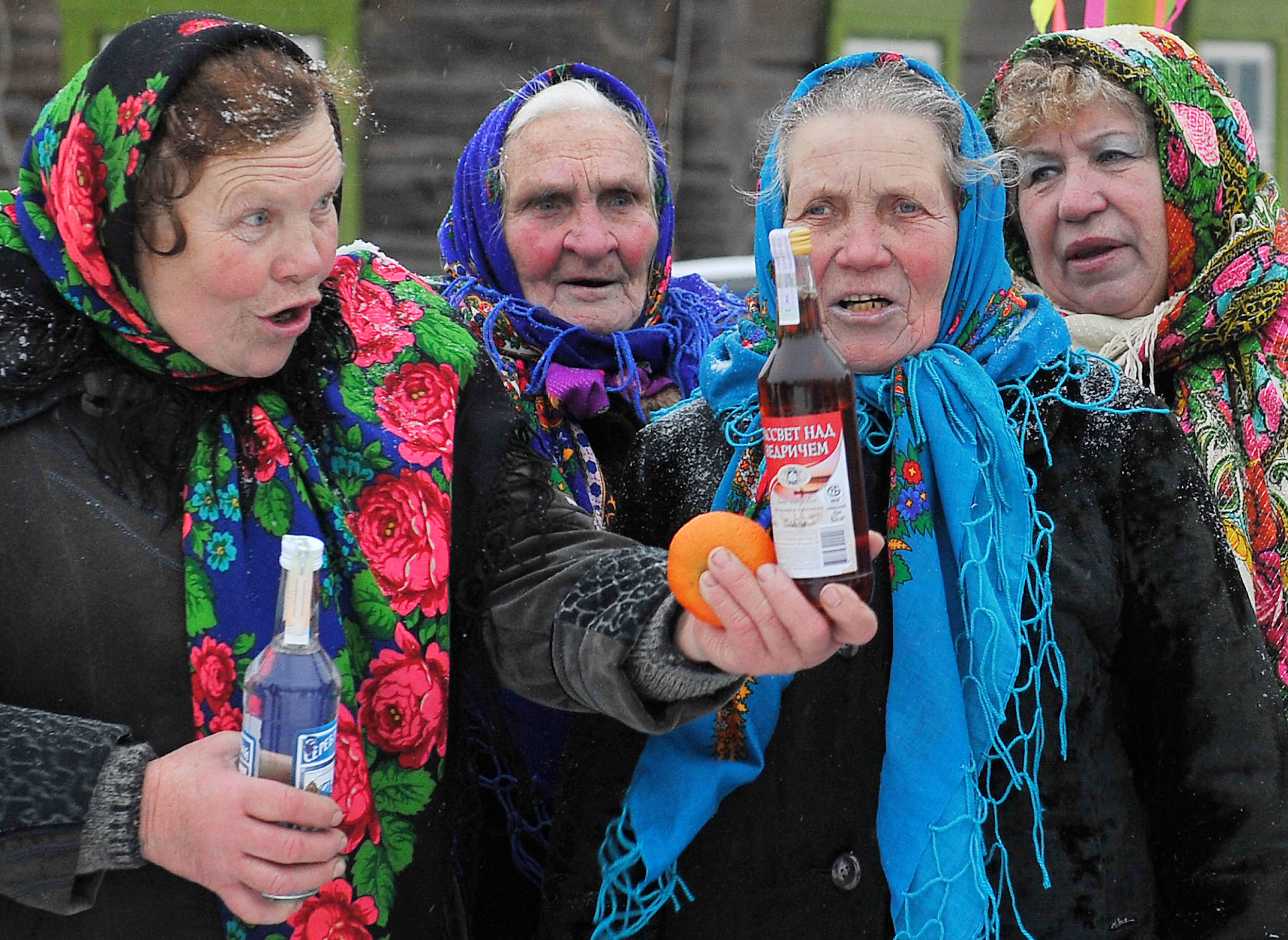 People drink vodka as they celebrate the Christmas carol rite (Koliady) in the village of Pogost. (Photo credit should read VIKTOR DRACHEV/AFP via Getty Images)